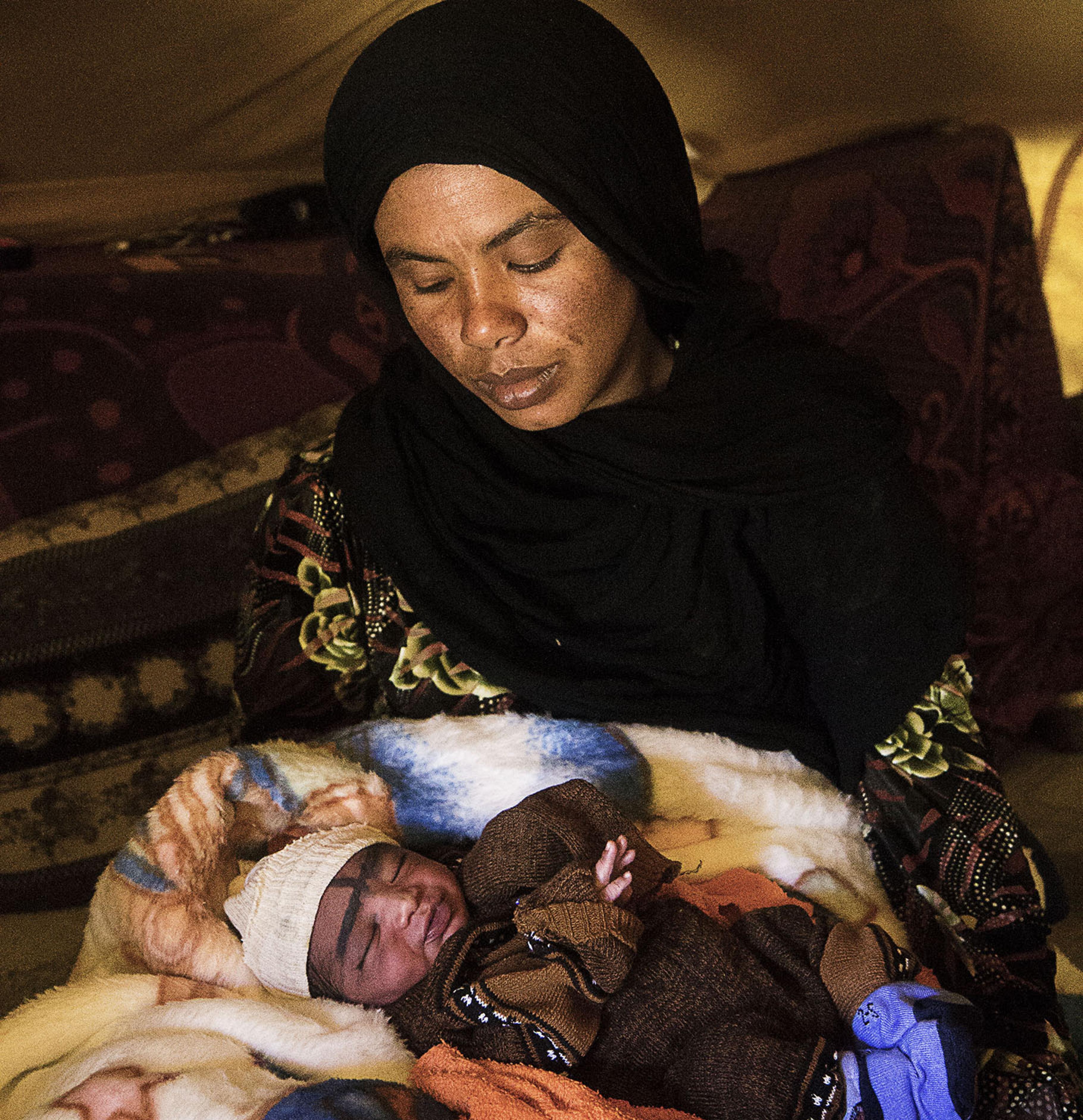 Hafsa hält ihr Neugeborenes im Arm