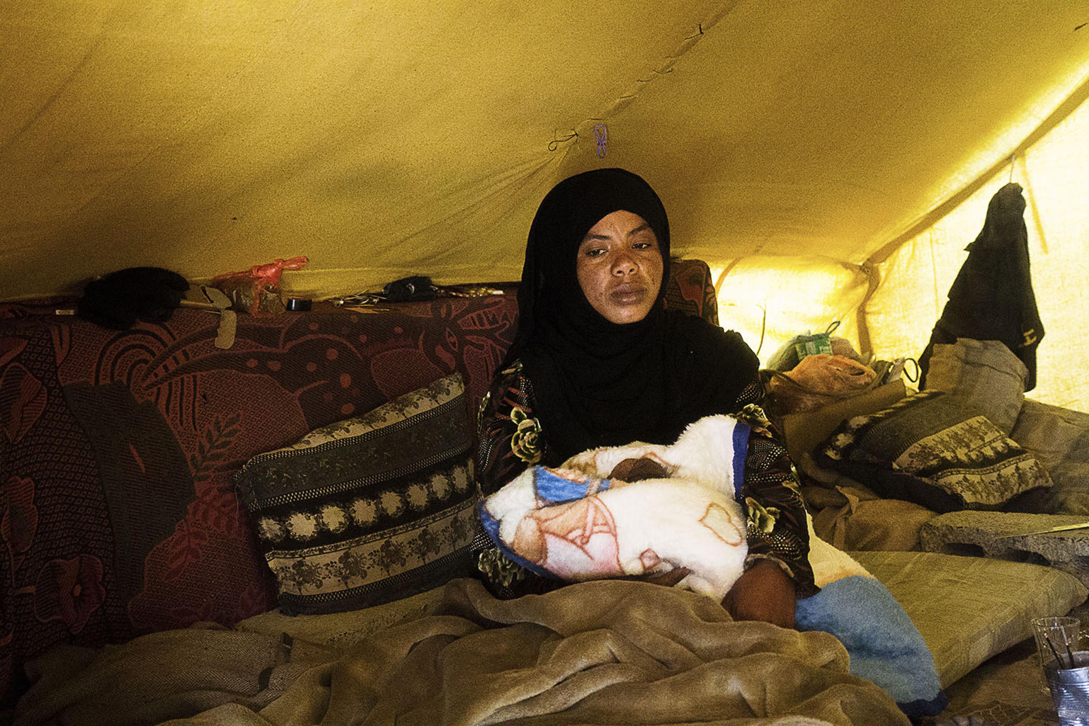 Hafsa sitzt mit ihrem Neugeborenen in einem Zelt