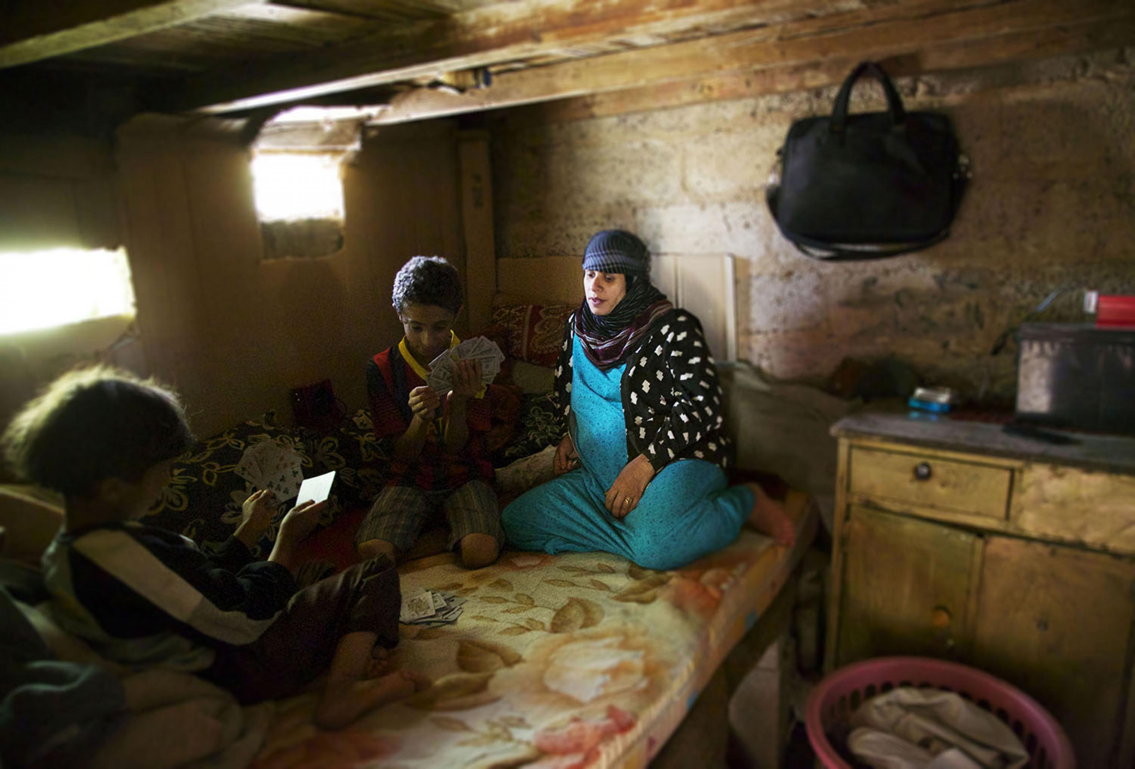 Katiba sitzt mit ihren Söhnen zusammen und spielt Karten.