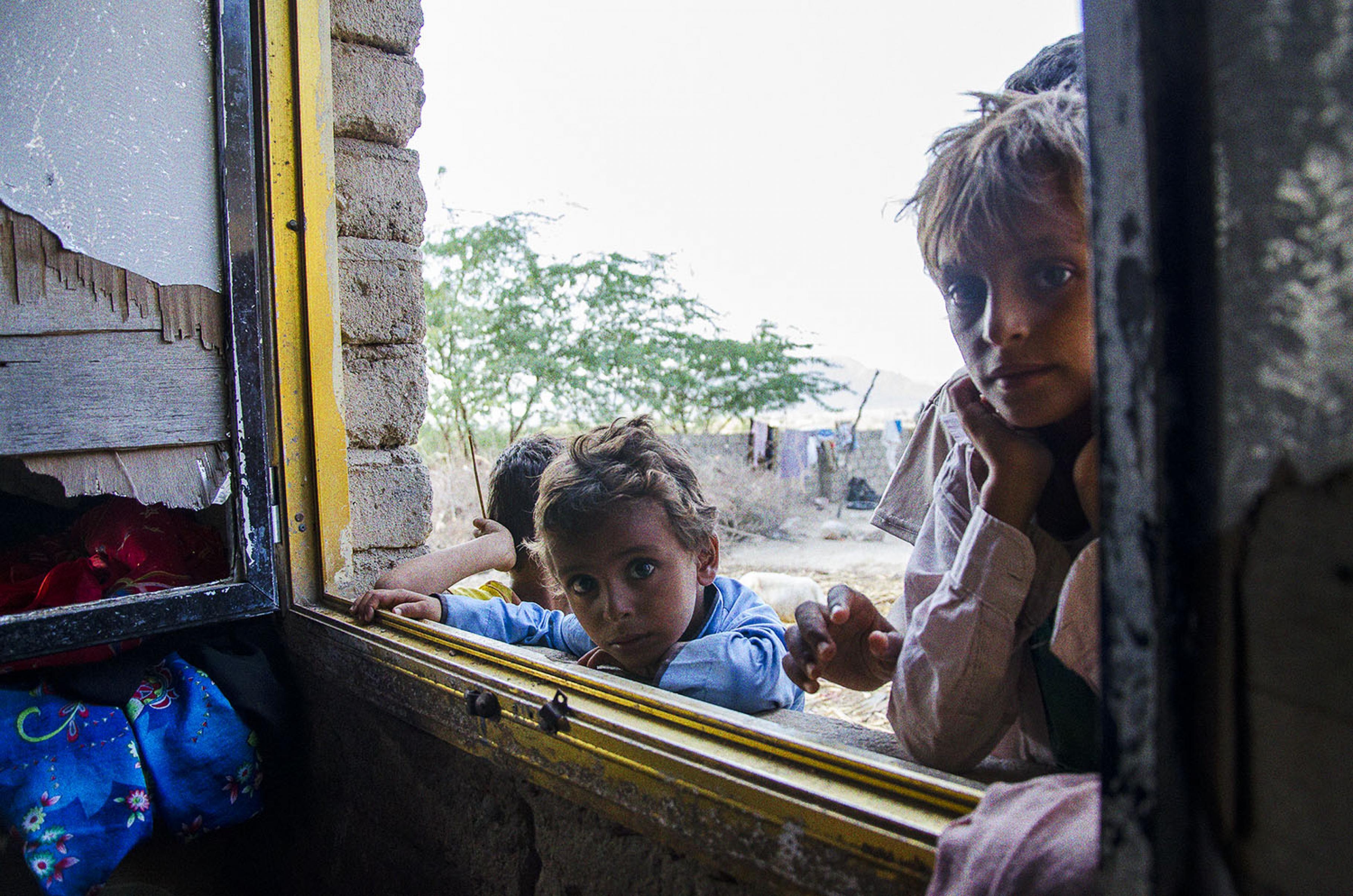 Kinder schauen durch Khamisas Fenster