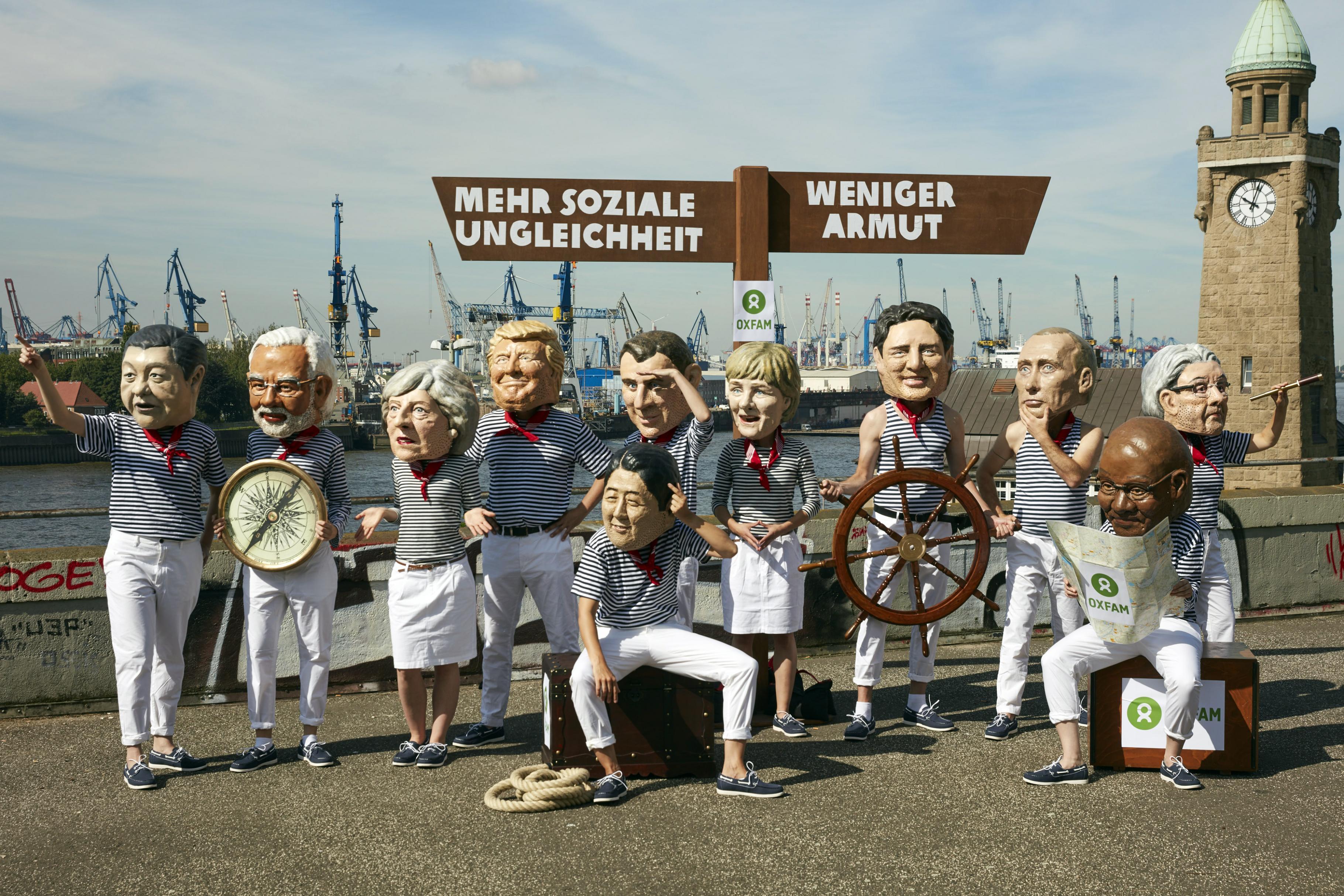 Oxfam-Aktivist/innen in überdimensionalen Masken einiger Staats- und Regierungschef/innen der G20 suchen nach dem Weg zu mehr sozialer Gerechtigkeit