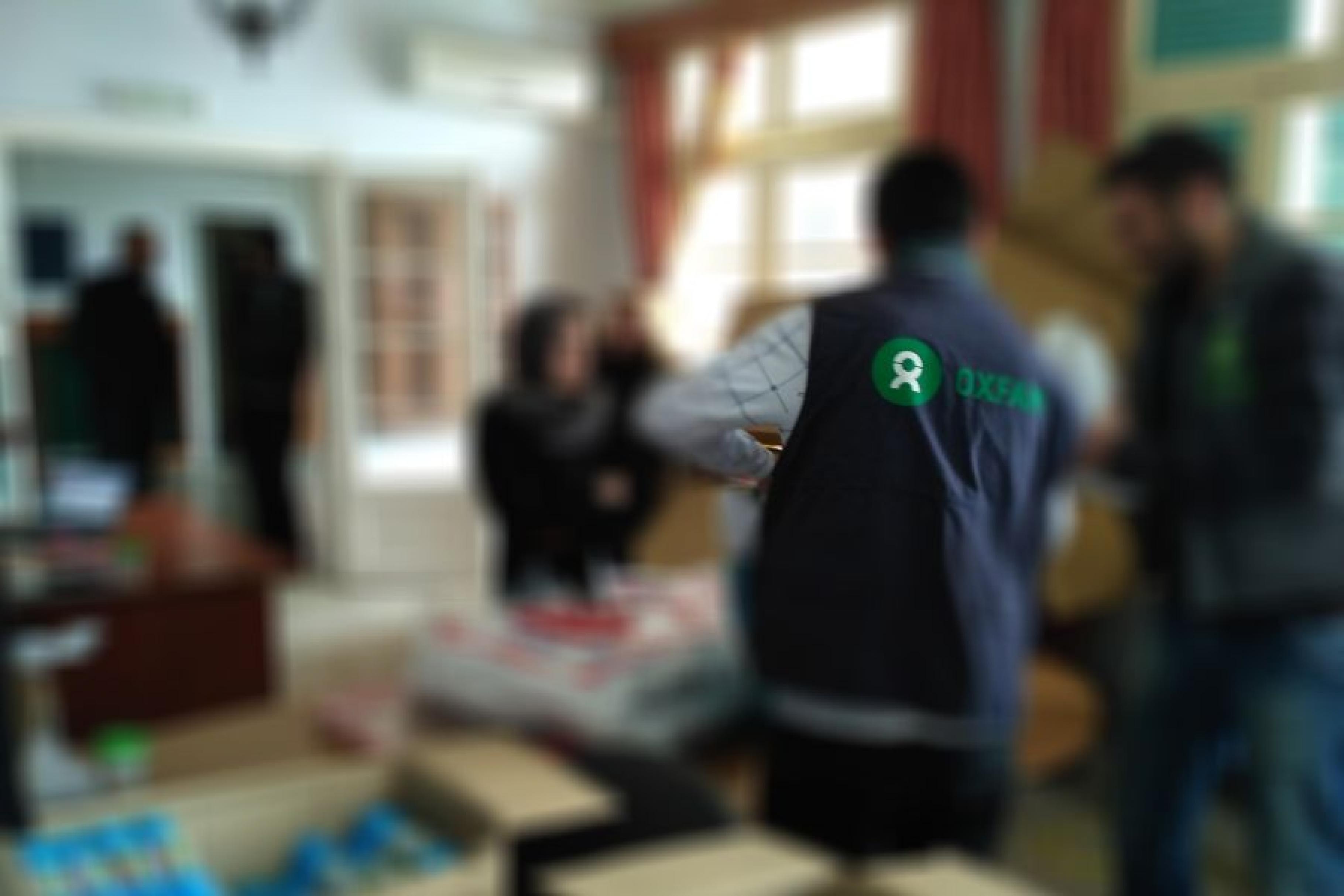Rückenansicht eines Oxfam-Mitarbeiters, der Hilfsgüter verteilt