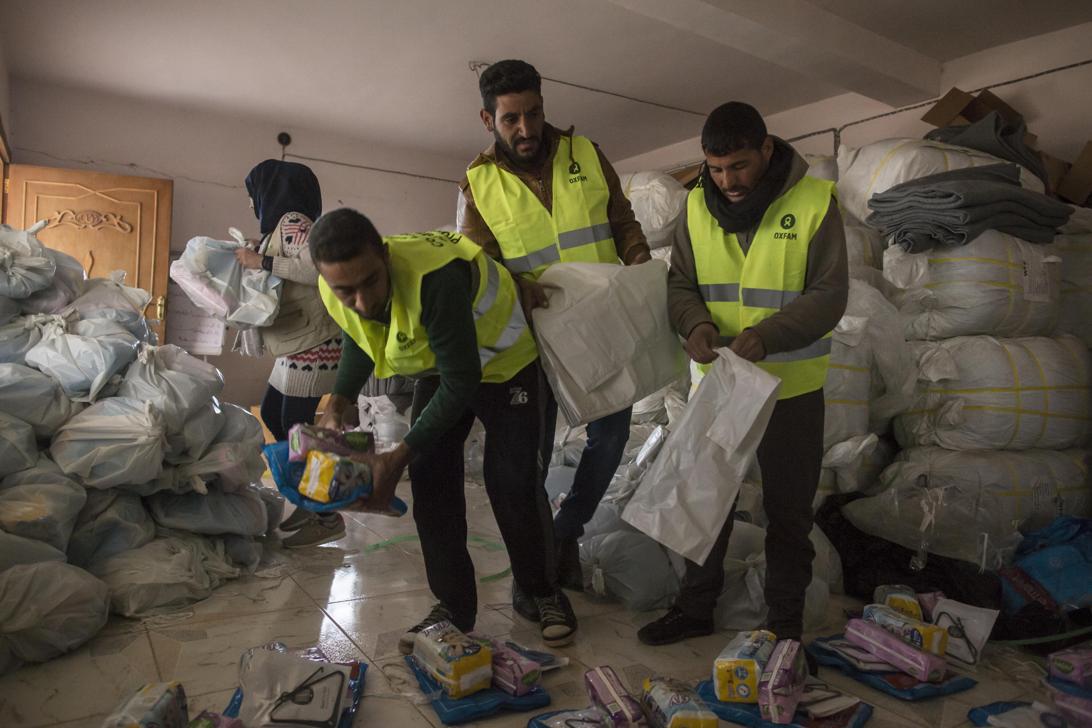 Drei Männder packen verschiedene Hilfsgüter in einem Plastiksack