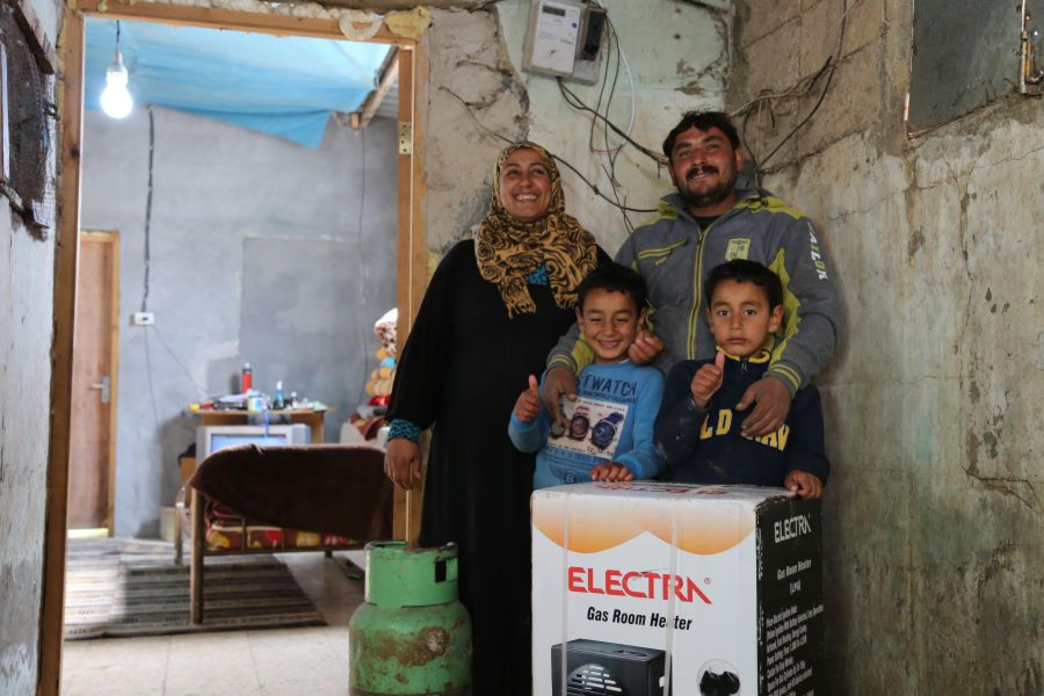 Eine Familie mit zwei Söhnen stehen vor einem noch verpacktem Heizgerät