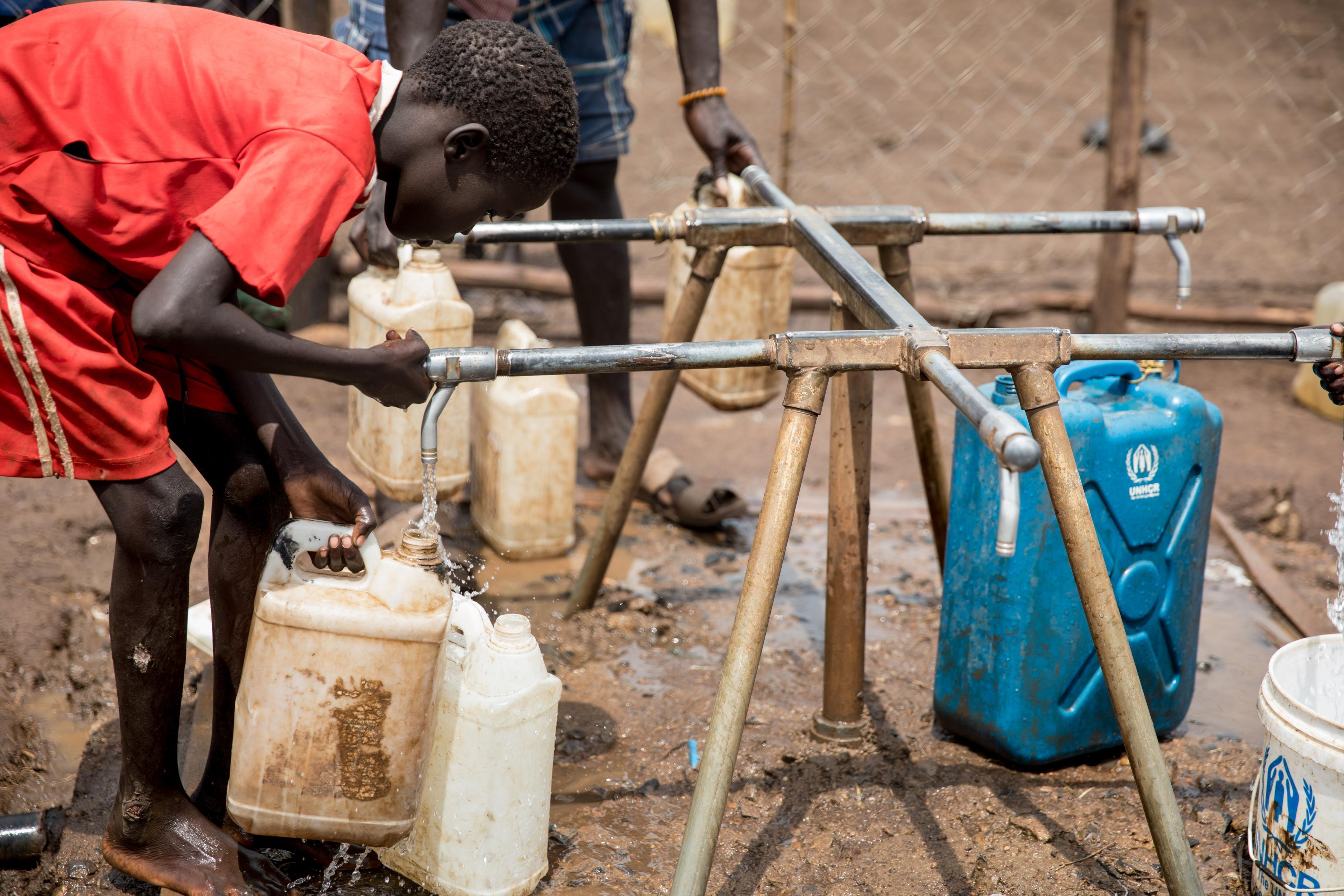 Ein Junge, der im Nguenyyiel Flüchtlingscamp lebt, füllt einen Kanister mit sauberem Wasser.