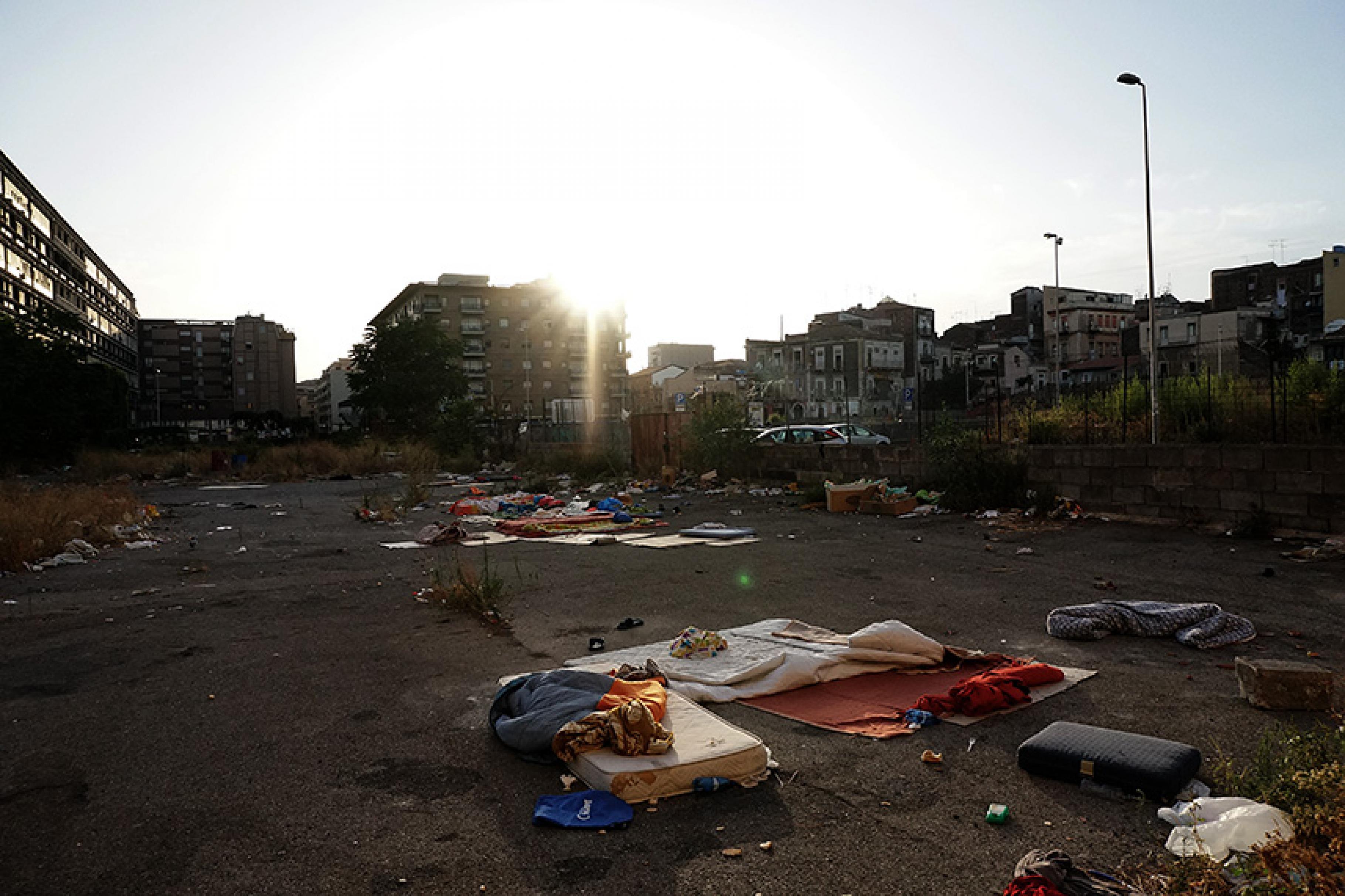 Notdürftige Schlafplätze umringt von Müll auf einer verwahrlosten Brache