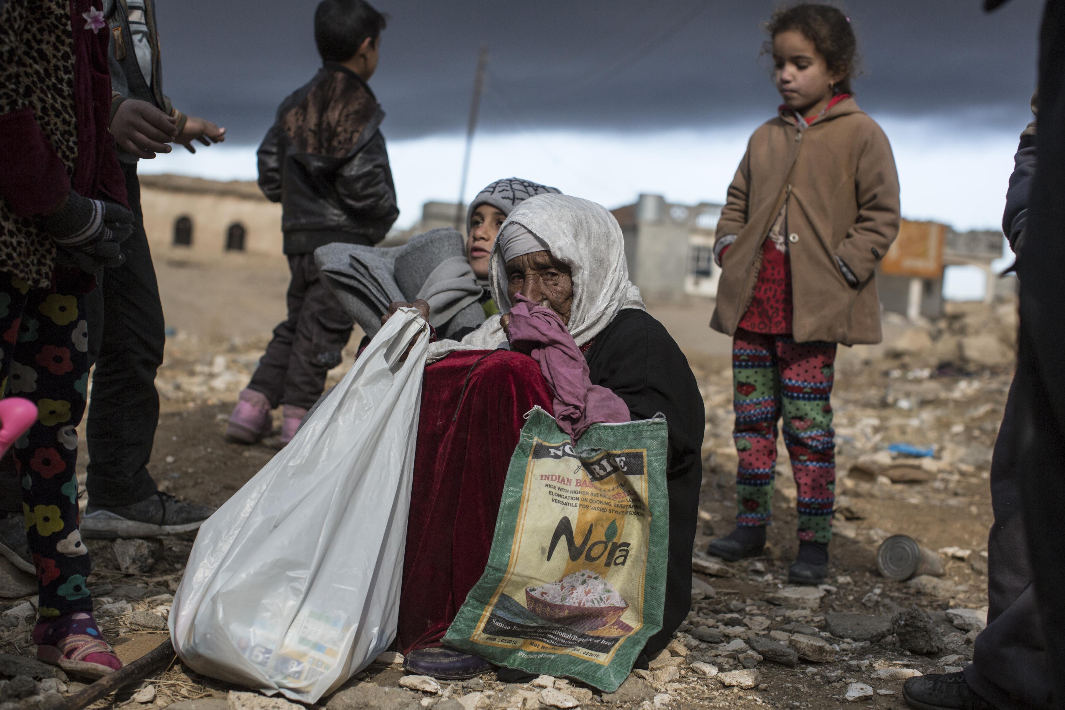 Eine alte Frau hockt auf dem Boden, in der Hand hält sie zwei Tragetaschen. Im Hintergrund sind ein paar Kinder zu sehen