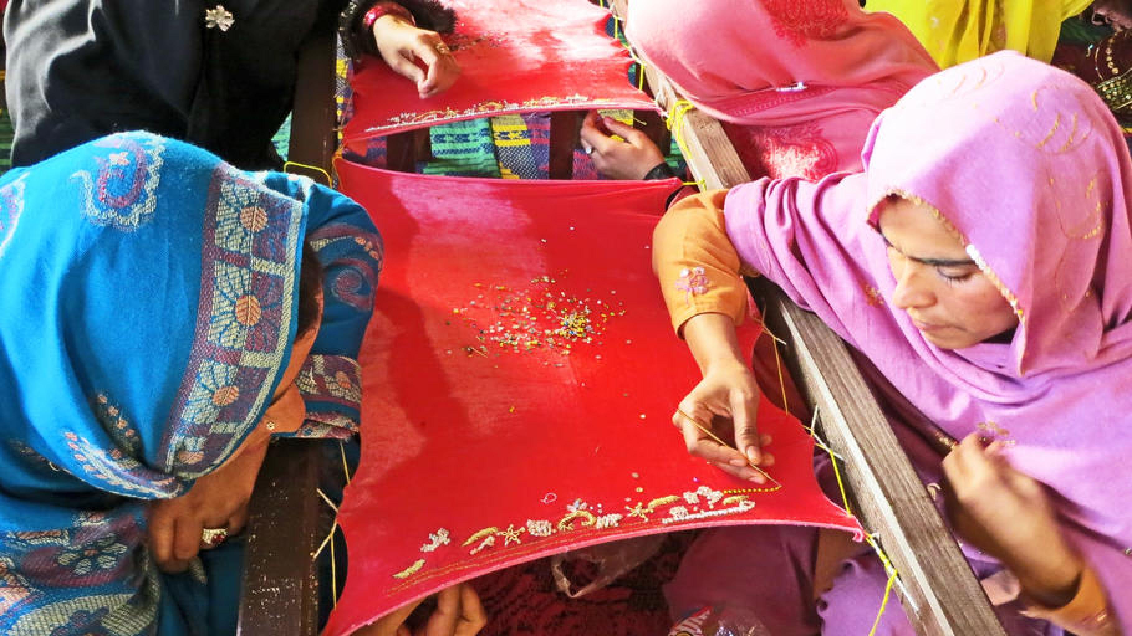 Zwei pakistanische Frauen sitzen über einen Stickrahmen gebeugt und sticken