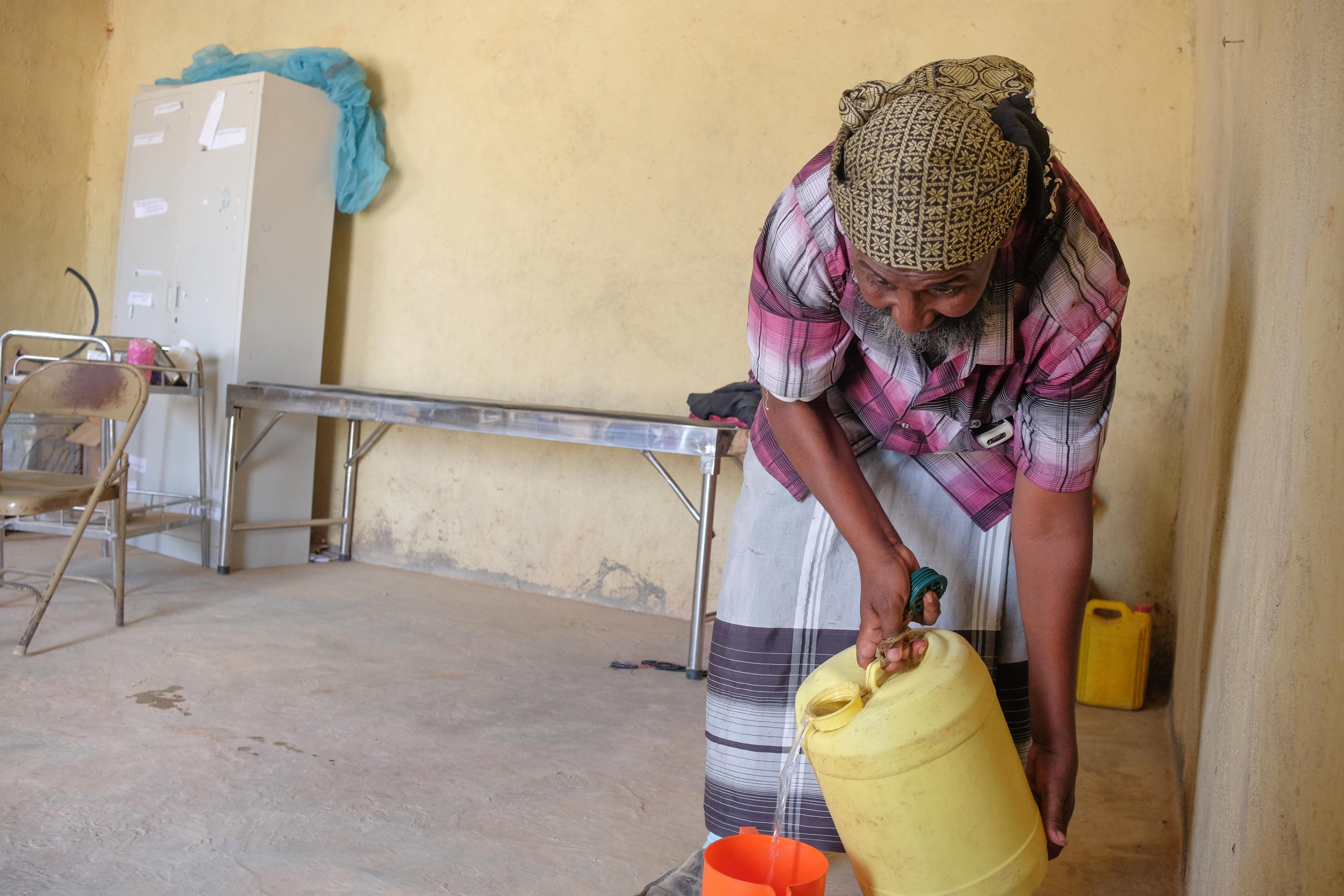 Abdile mischt Wasser mit einem Elektrolyt-Sirup, der einer Dehydrierung vorbeugen soll.