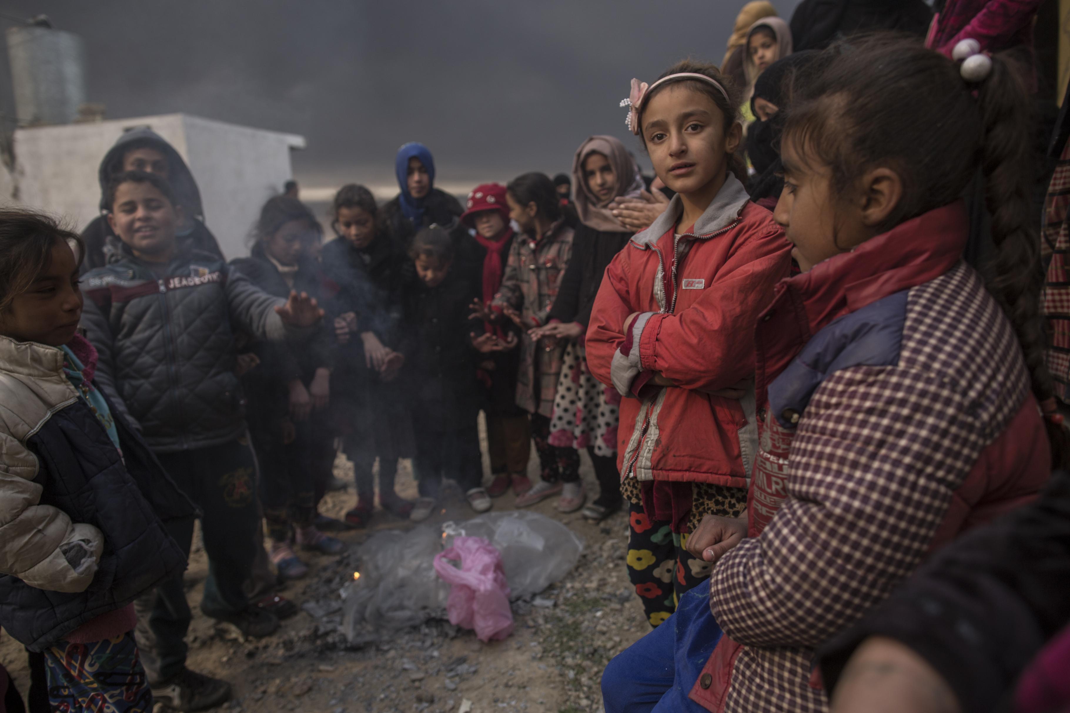 Kinder wärmen ihre Hände an einem kleinen Feuer, indem Plastiktüten verbrannt werden