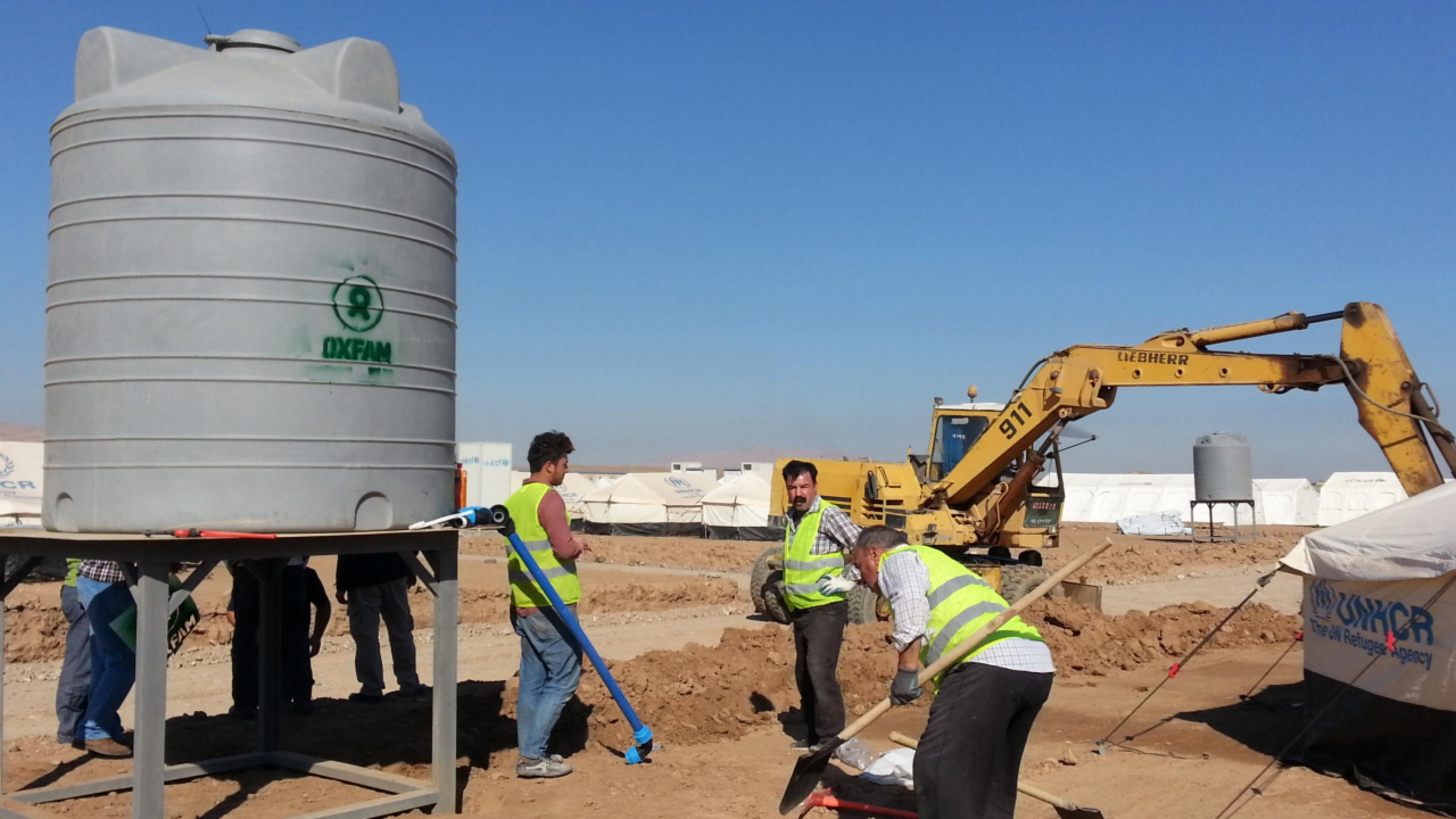 Oxfam-Mitarbeiter an einem Tank mit sauberem Wasser im Hassansham-Camp, etwa 50 Kilometer östlich von Mossul