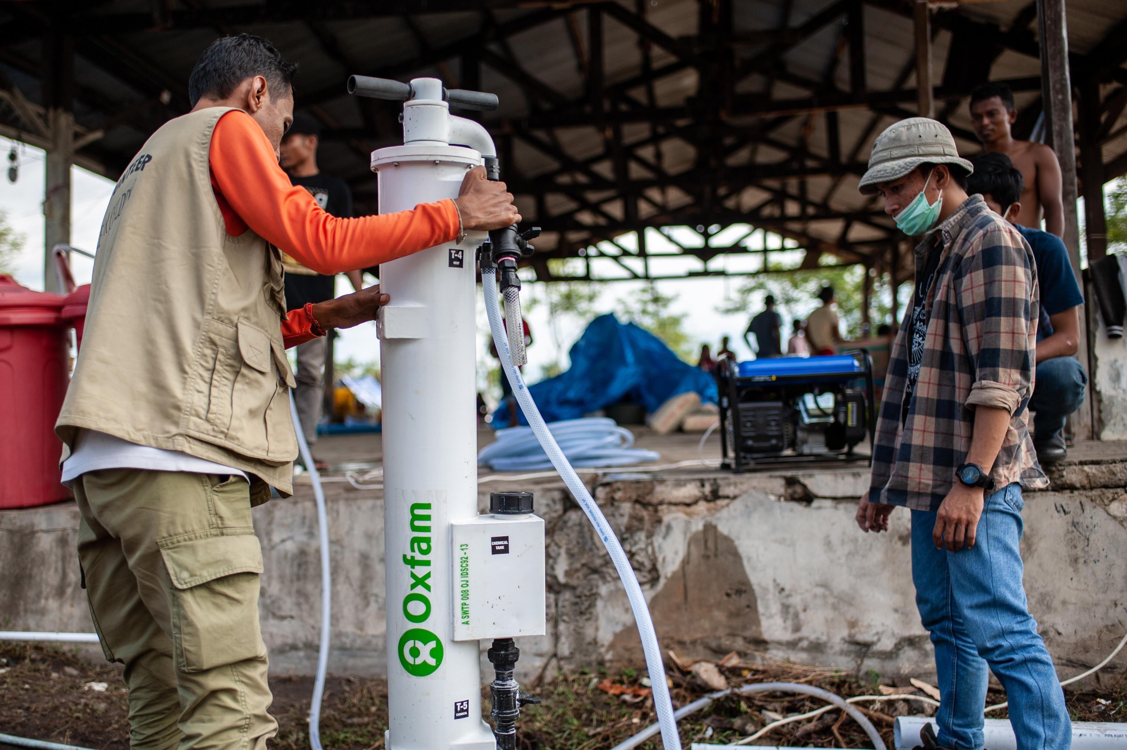 Ein Mann installiert einen Wasserfilter, der annähernd so hoch ist wie er selbst.