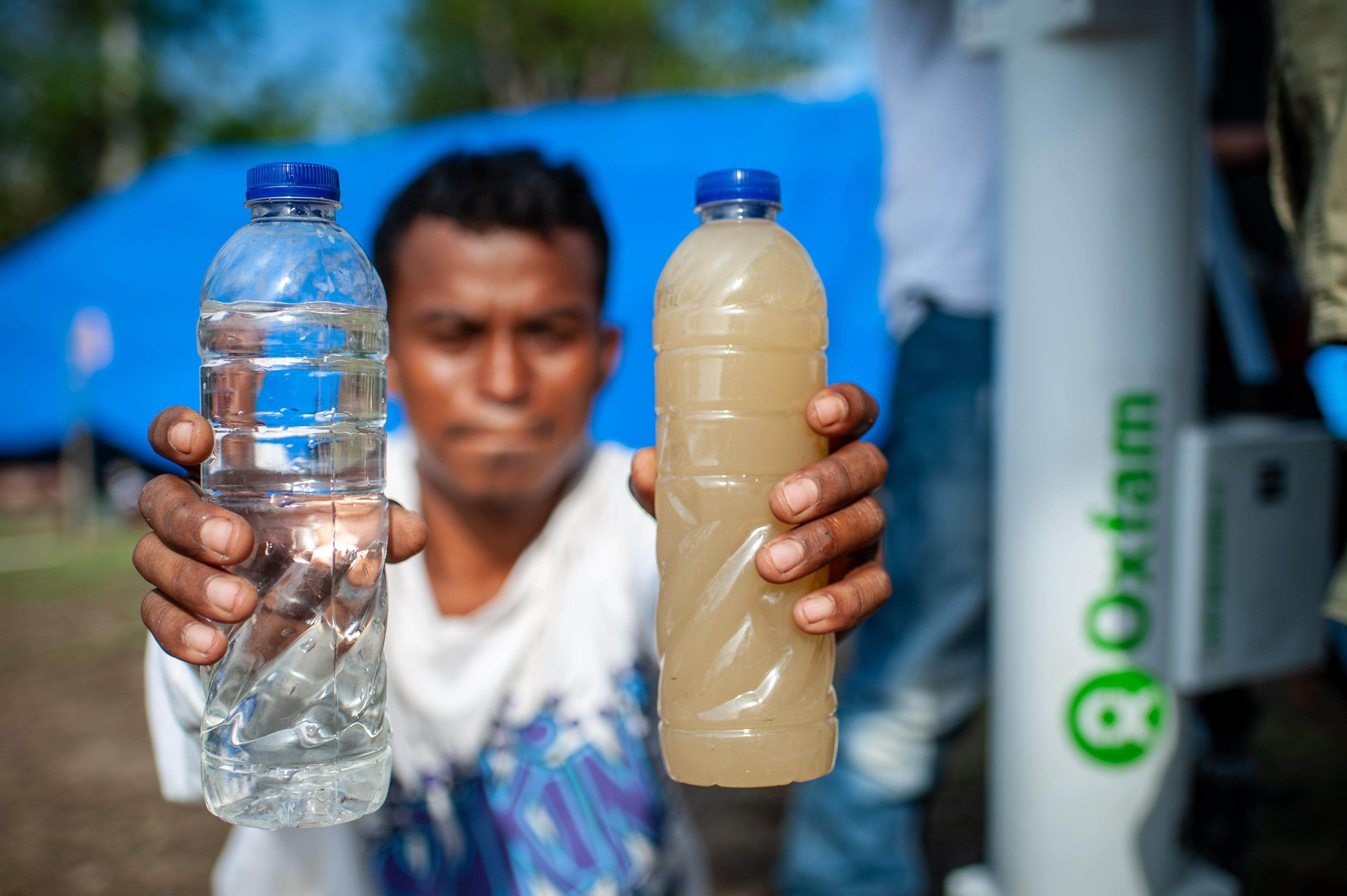 Ein Mann zeigt eine Flasche mit sauberem und eine mit schmutzigem Wasser