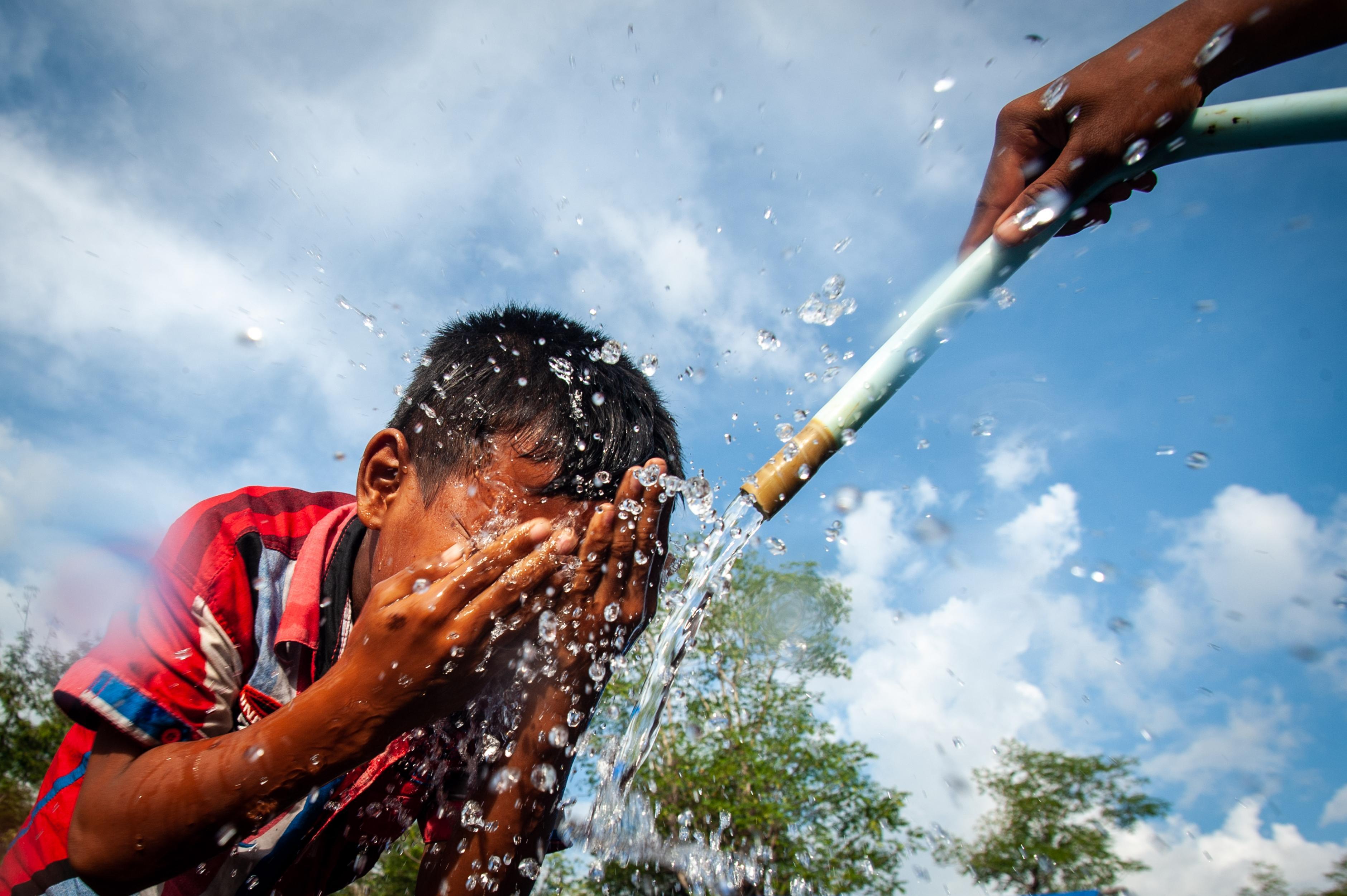 Ein Junge wäscht sich das Gesicht unter einem Wasserschlauch.