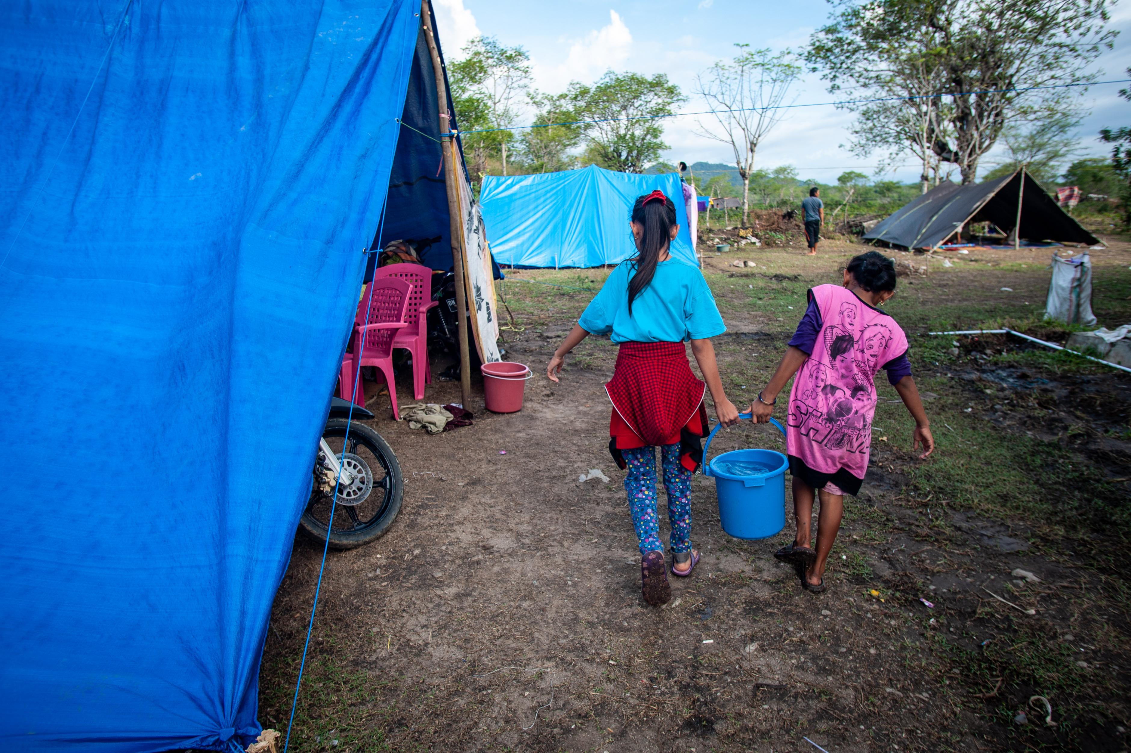 Zwei Mädchen tragen einen Eimer Wasser zwischen Zelten.
