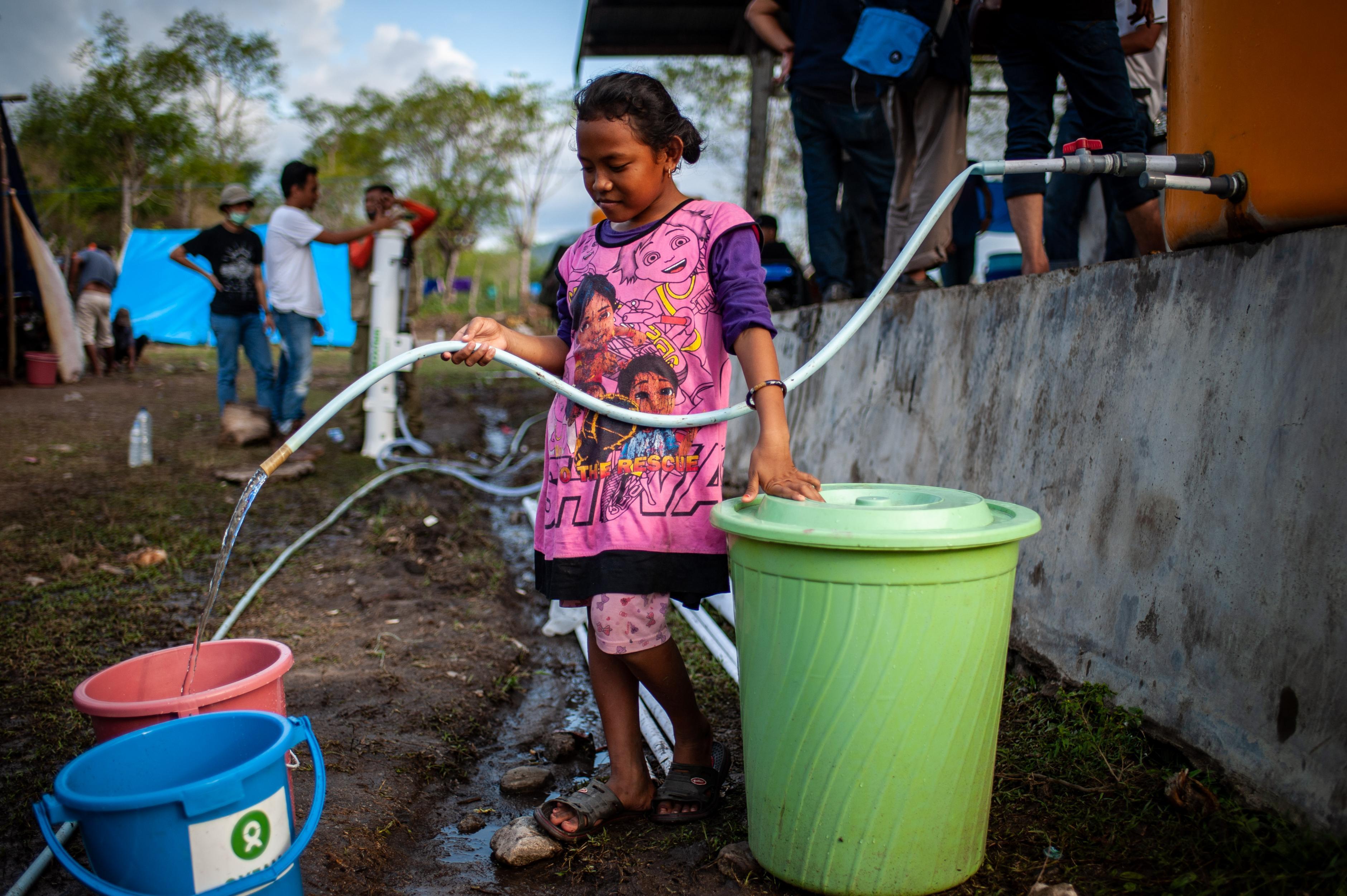 Ein Mädchen füllt Wasser aus einem Fass in einen Eimer.