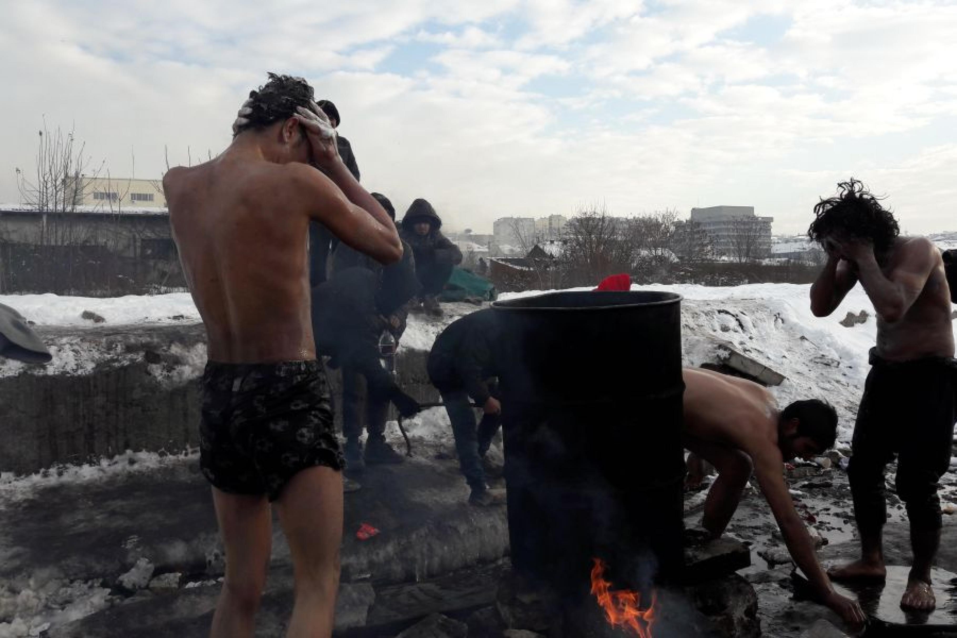 Männer stehen auf einer schneebedeckten Brachfläche um eine Feuertonne und waschen sich