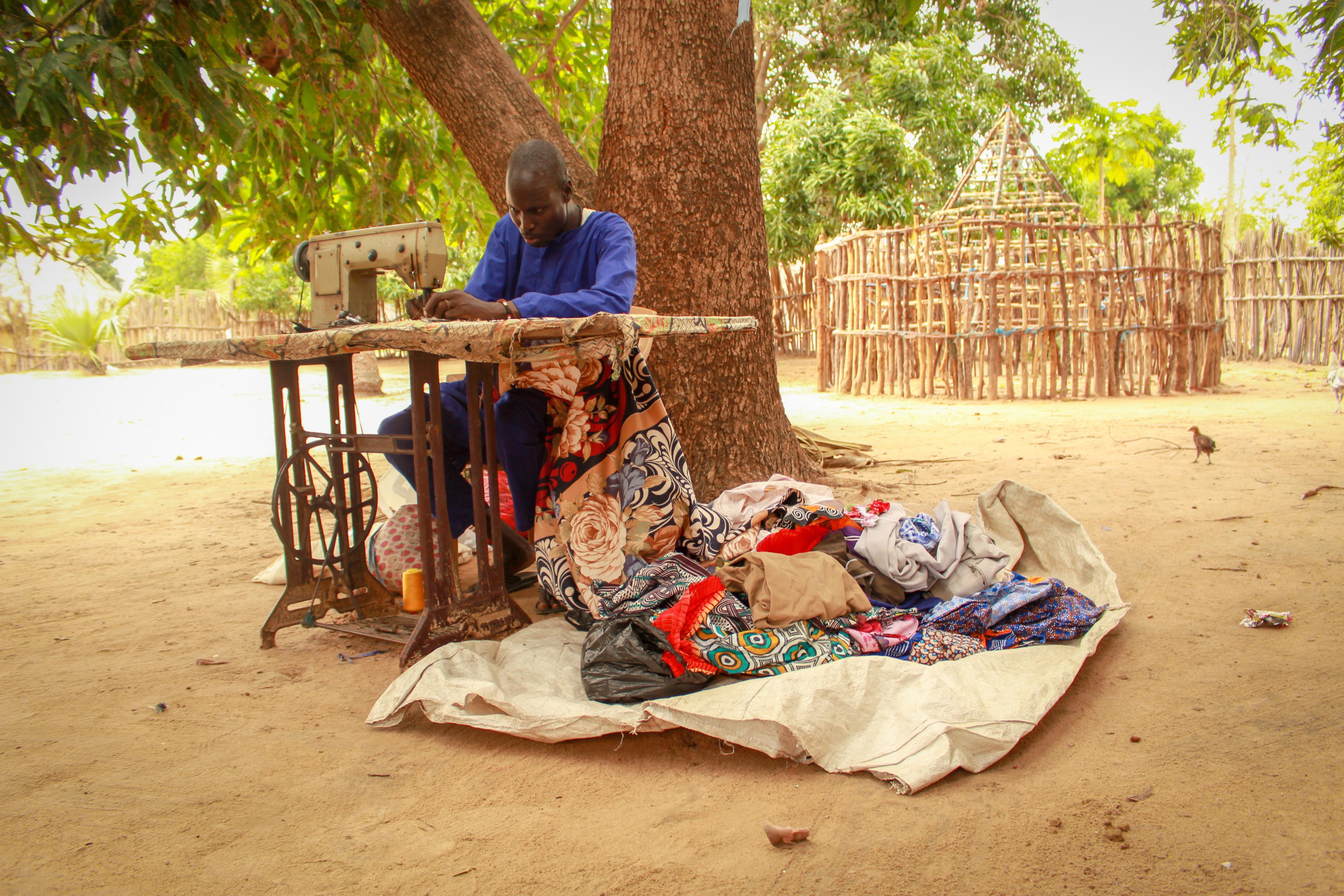 Peter an seiner Nähmaschine unter einem Mangobaum