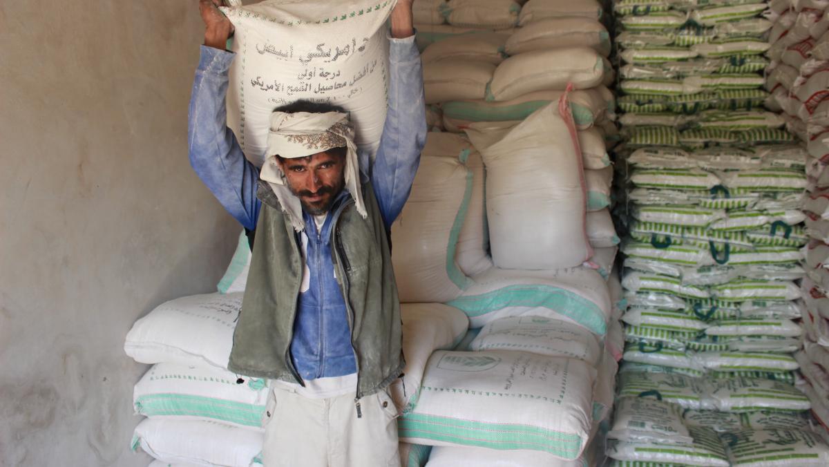 Ein Mann aus dem Jemen trägt einen Sack mit Weizen