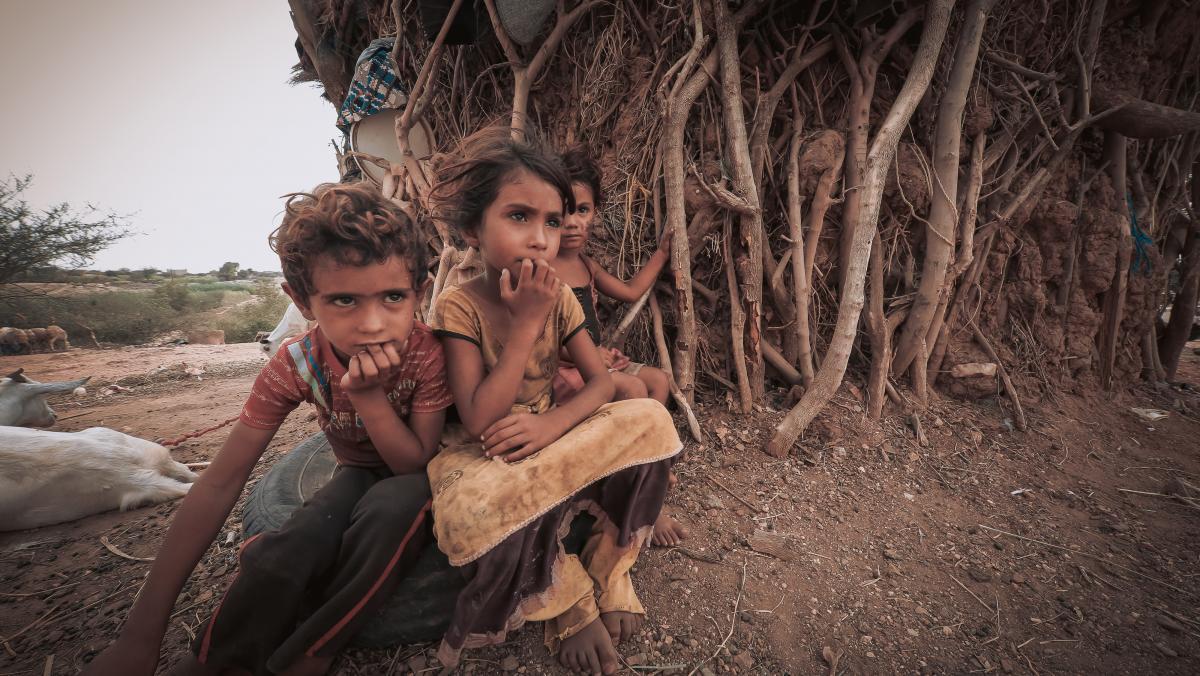 Drei Kinder sitzen vor einer einfachen Unterkunft aus Holz und abgenutzten Tüchern