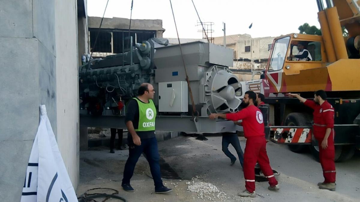 Mitarbeiter von Oxfam und des Roten Halbmonds entladen einen Generator