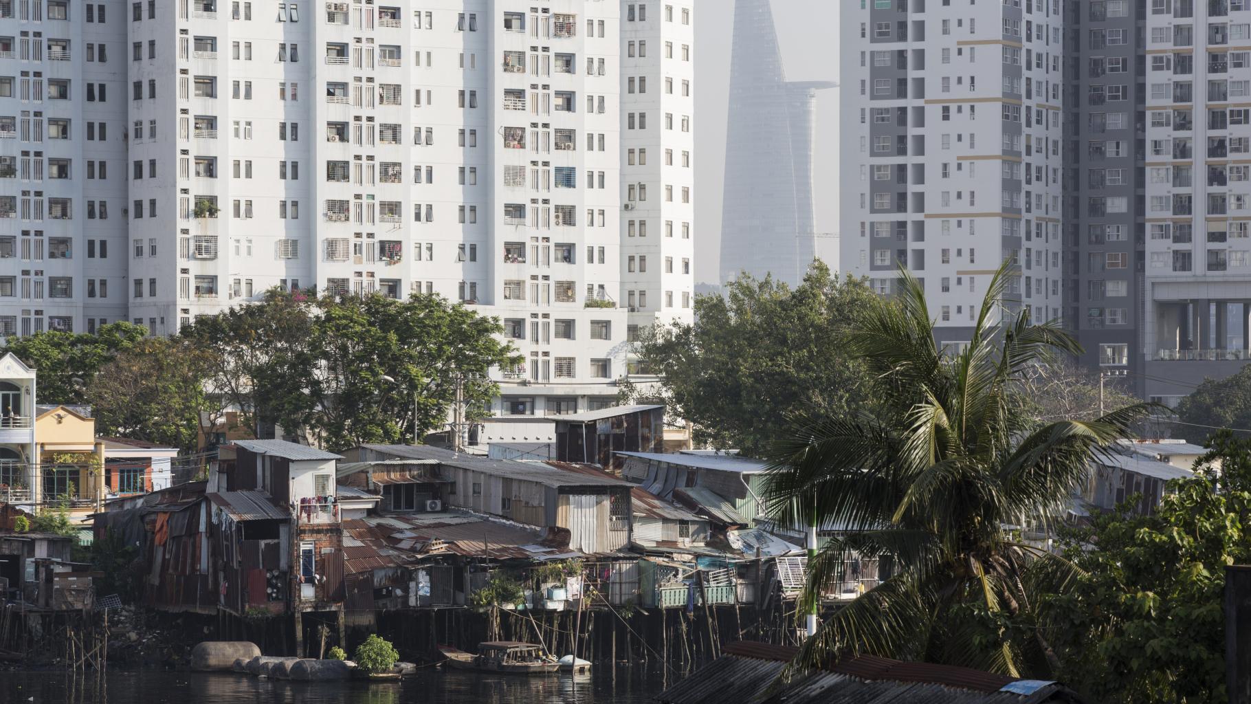 Notdürfitge auf Baumstämmen am Flußufer erbaute Unterkünfte, im Hintergrund moderne Wohn-und Bürogebäude und der Bitexco Financial Tower