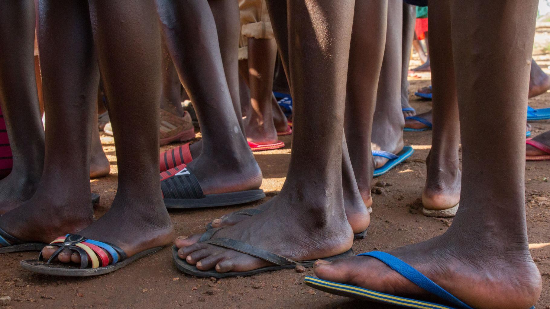 Füße von Schüler*innen einer Grundschule im Flüchtlingscamp Bidi Bidi in Uganda