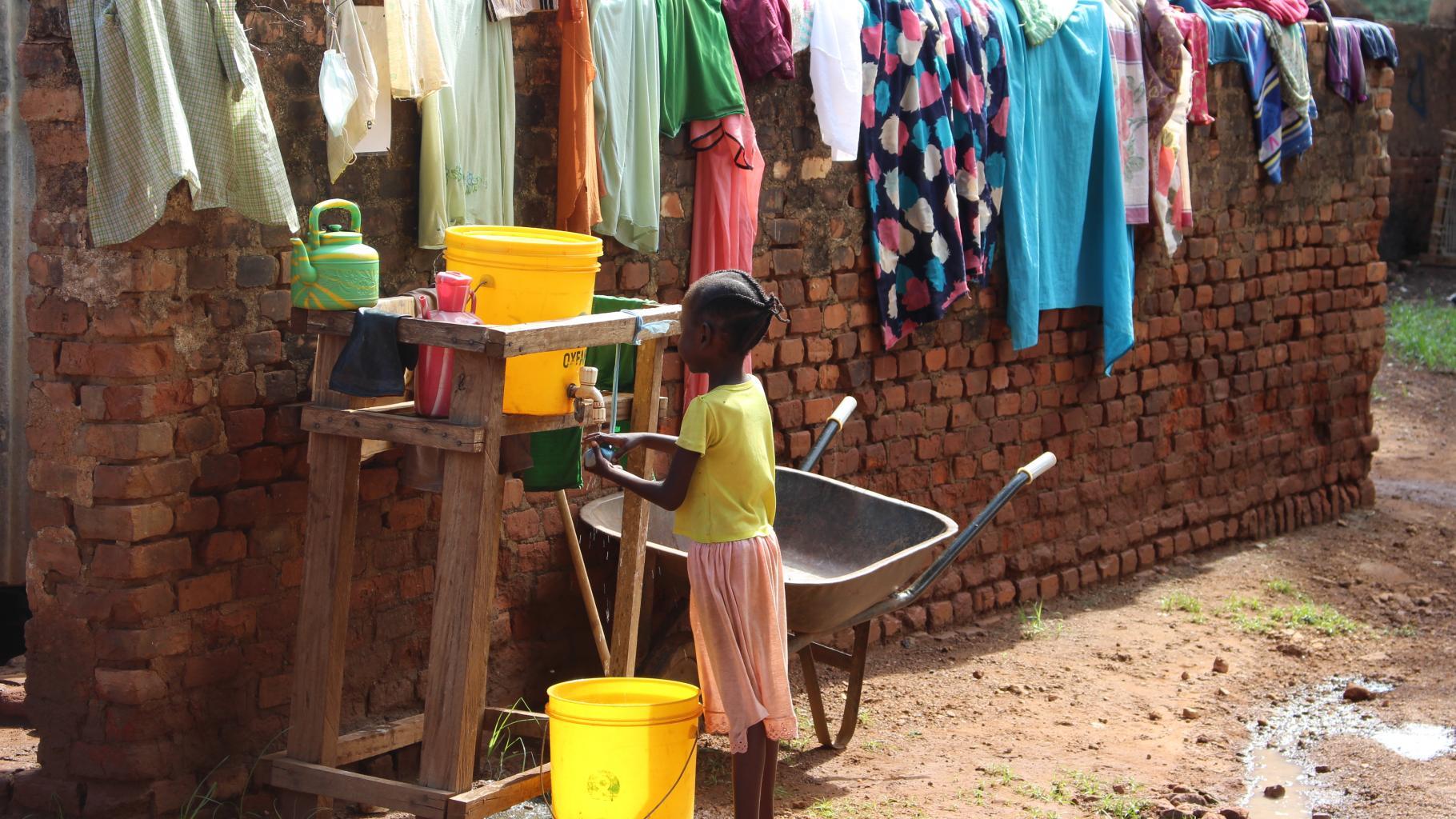 Junges Mädchen an Wasserstelle im Lager in Wau, Südsudan