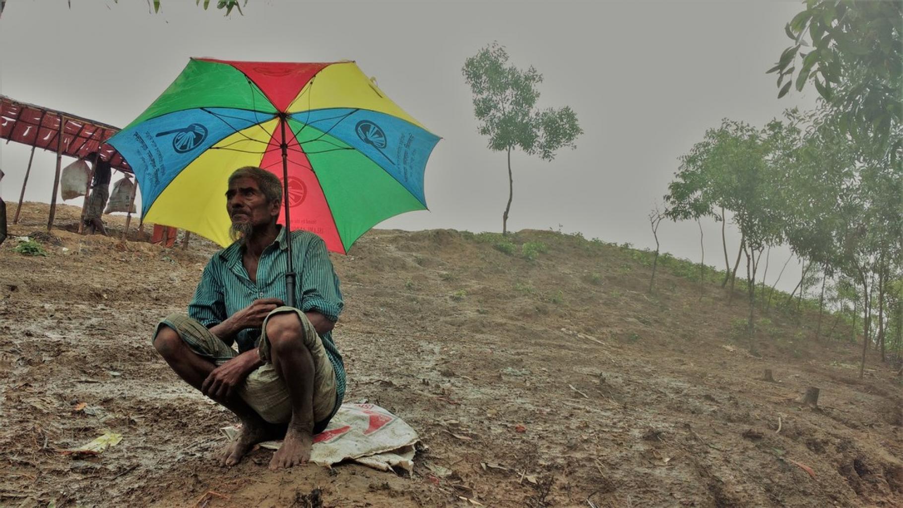 Rohingya-Mann mit Regenschirm auf Hügel