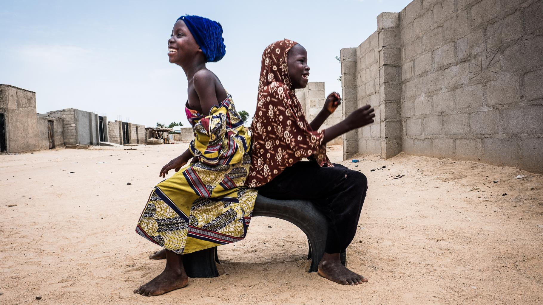 Zwei Mädchen sitzen auf einem Autoreifen auf einer Straße Nigeria