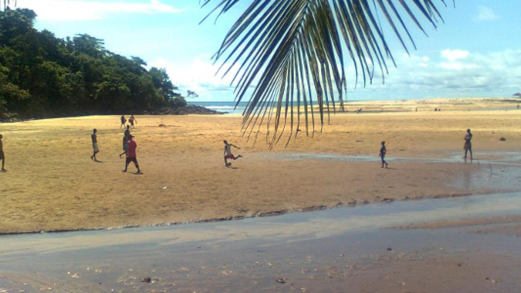 Foto: Jungen spielen Fußball an einem Strand.