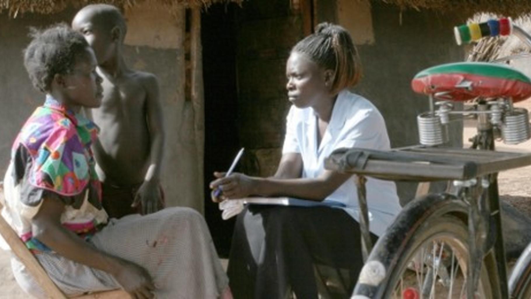 Foto: eine Gesundheitsberaterin in Uganda bei einem Hausbesuch