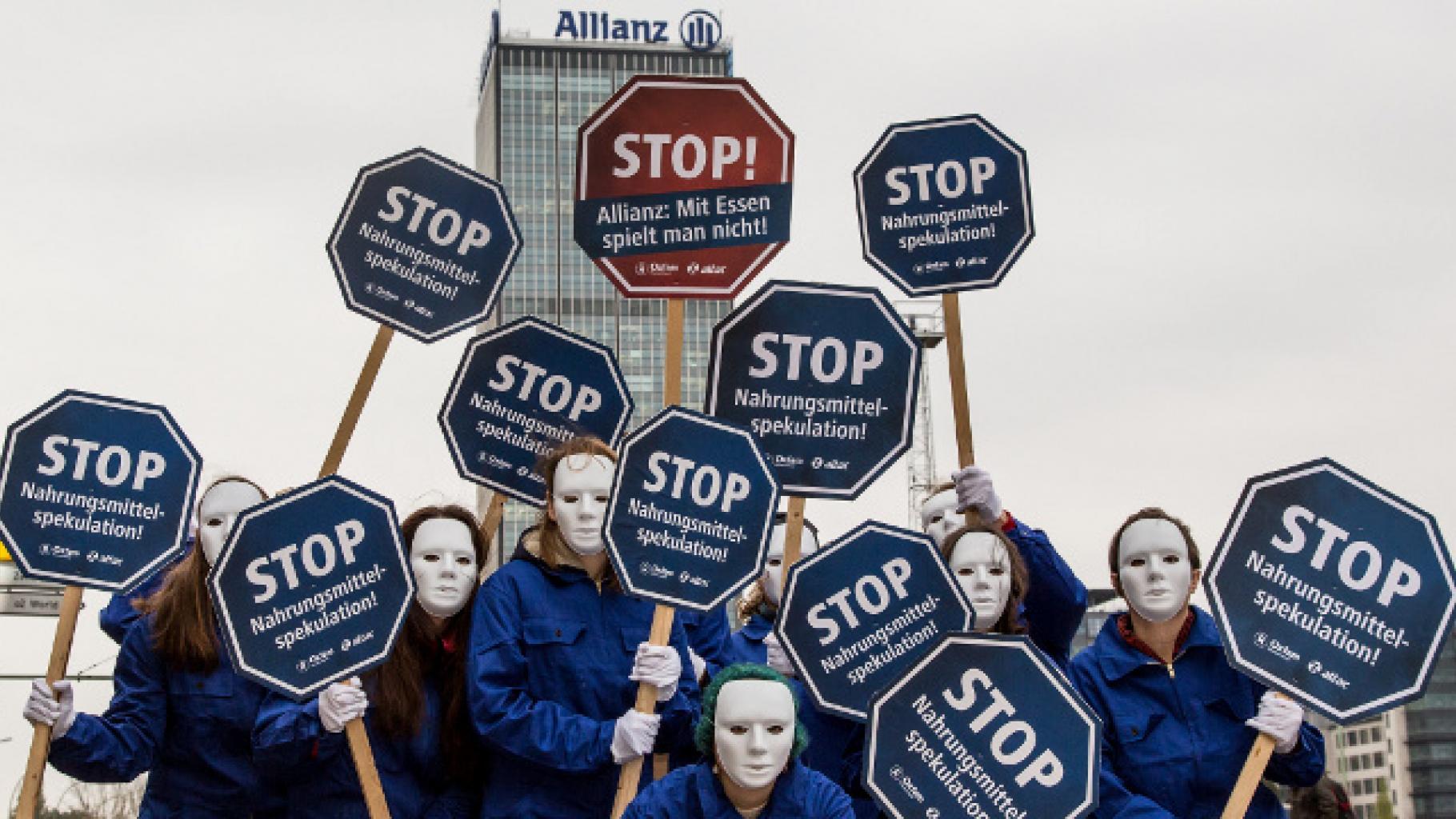 """Demo mit Schildern: """"Nahrungsmittelspekulation stoppen!"""" vor Allianz-Gebäude"""