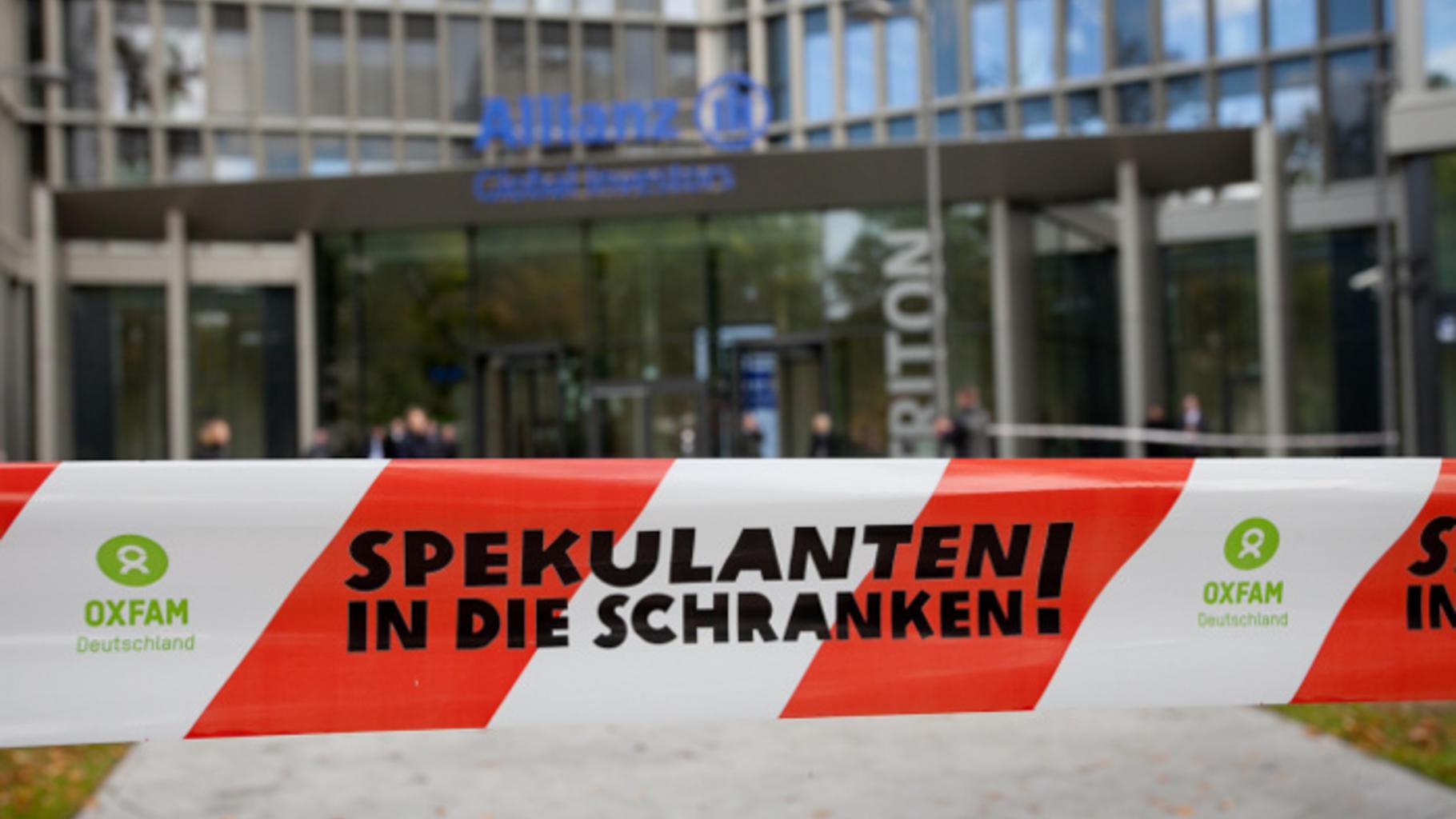 """Absperrband mit Aufschrift """"Spekulanten in die Schranken!"""" vor Allianz-Zentrale"""