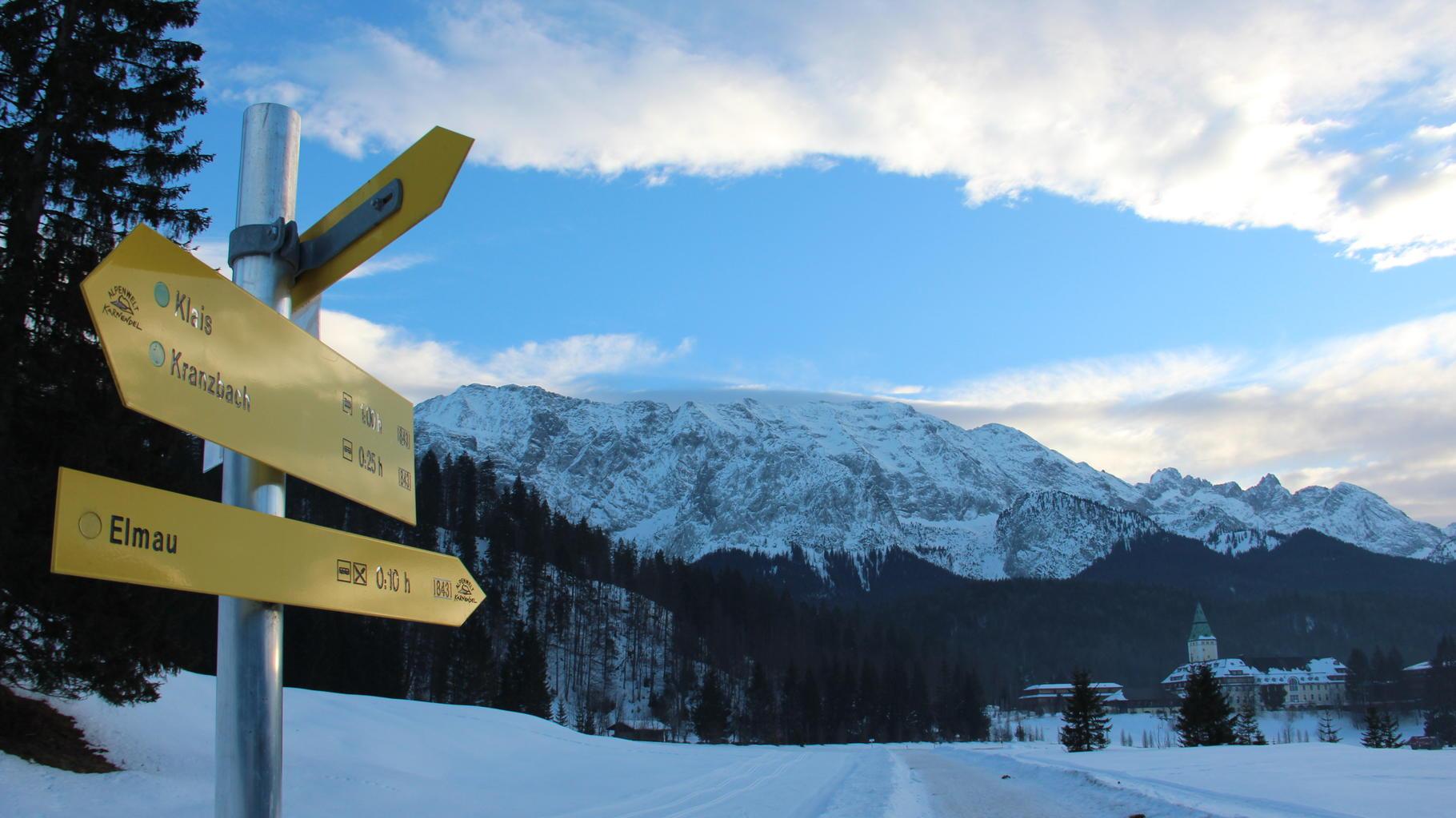 Wegweiser nach Elmau in einer schneebedeckten Alpenlandschaft