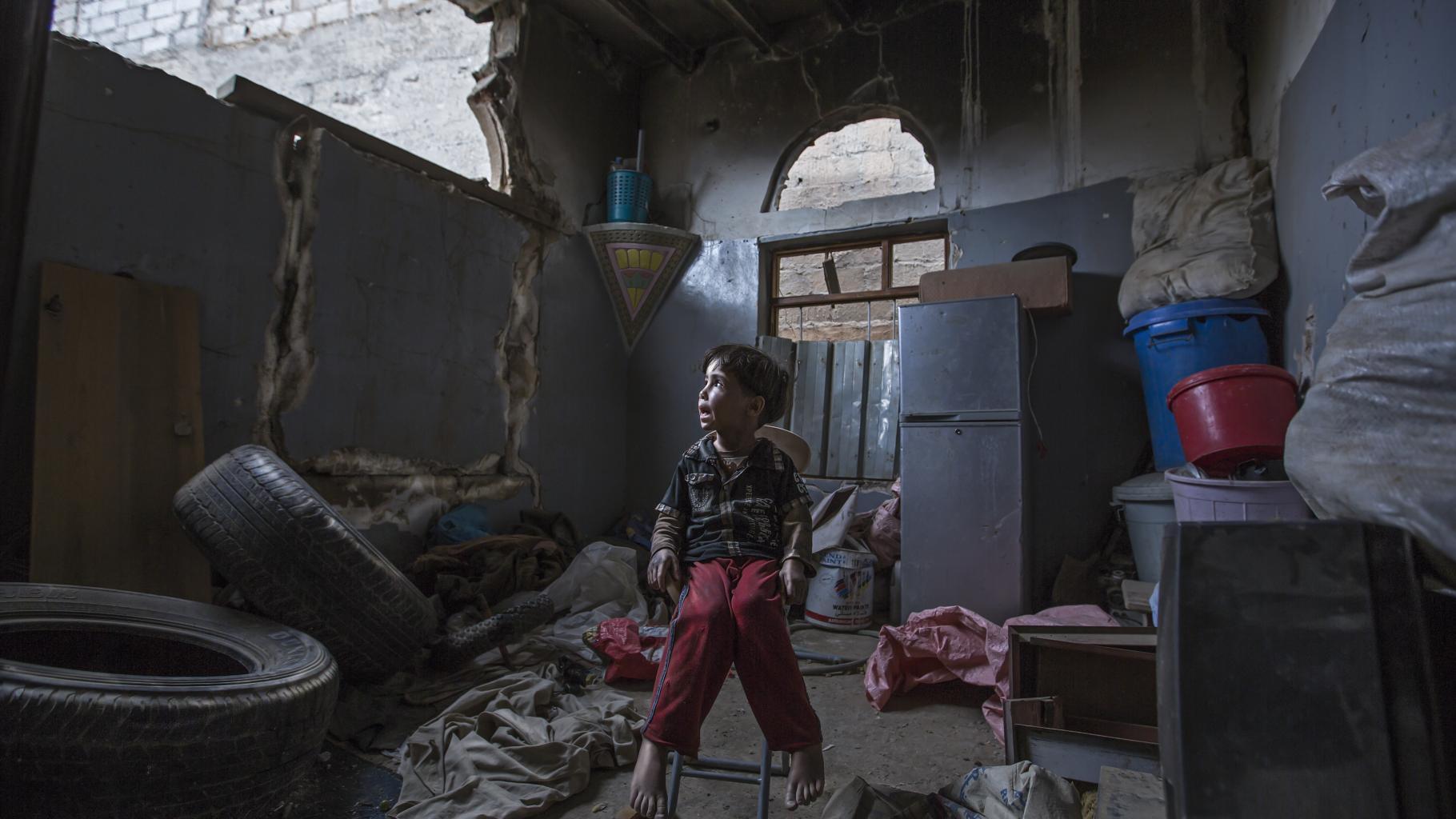 Ein Kind sitzt in seinem Zuhause, das durch einen Luftangriff zerstört wurde