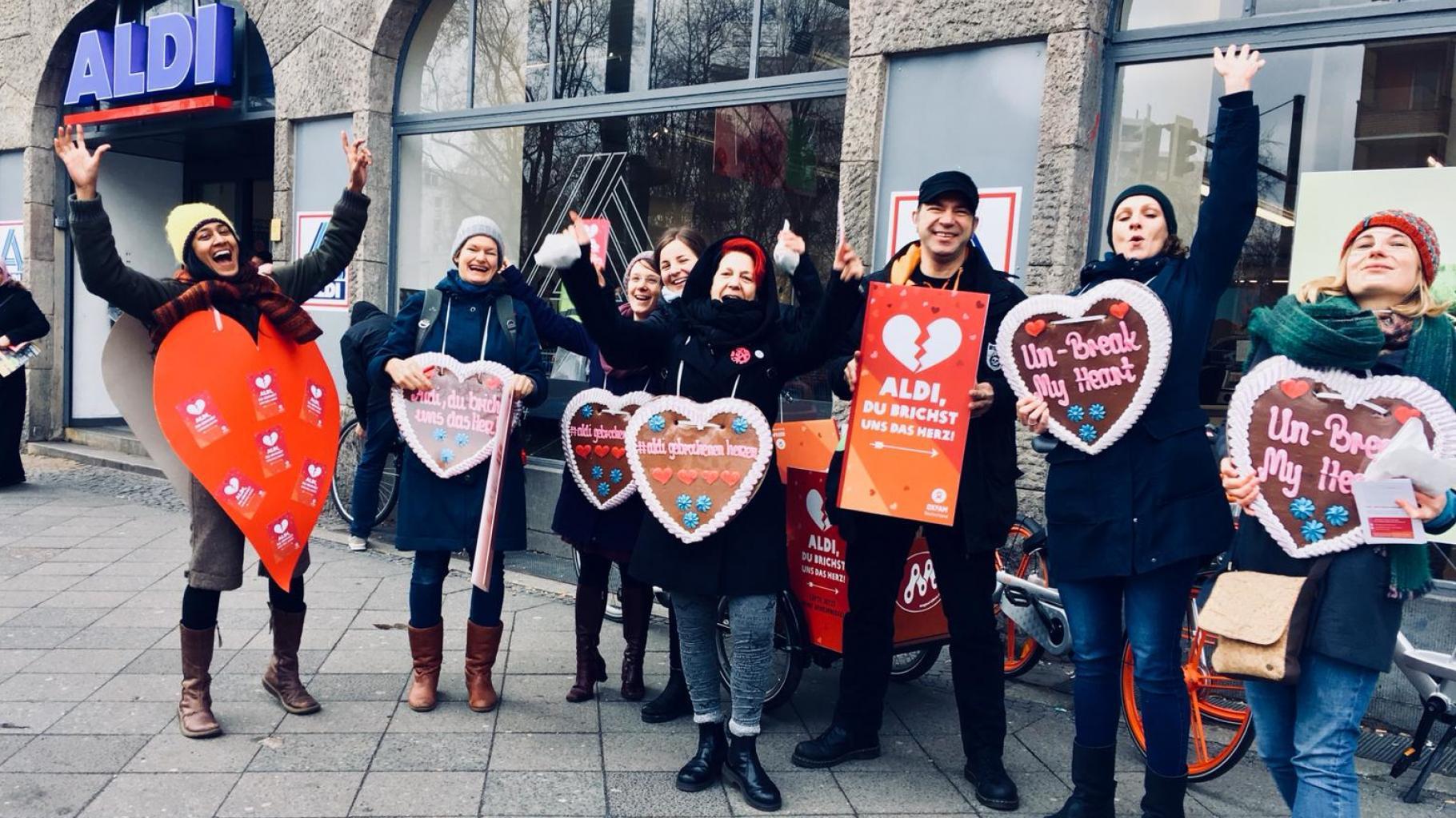 """Oxfam-Aktivist*innen vor einer Aldi-Filiale halten Plakate und Lebkuchenherzen mit der Aufschrift """"Aldi, du brichst uns das Herz"""", """"#aldigebrochenenherzen"""" und """"Un-Break My Heart"""""""