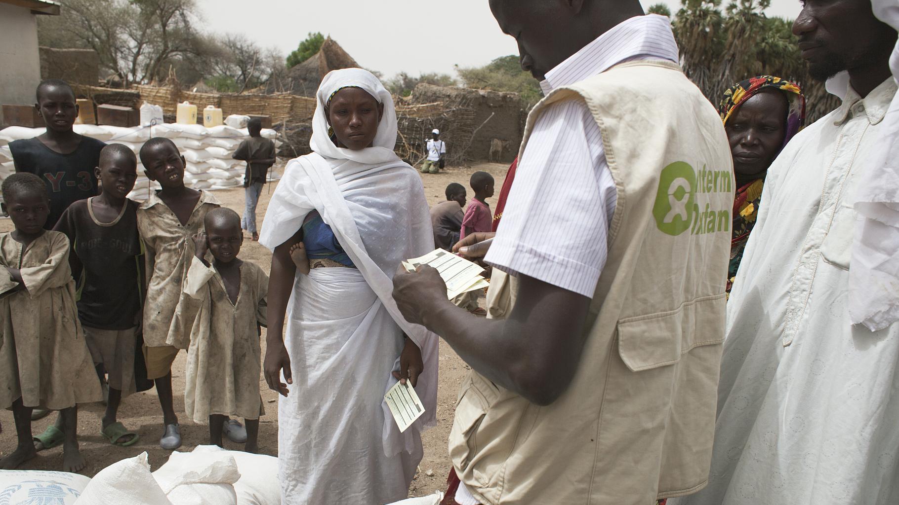 Eine junge Mutter und ein Oxfam-Mitarbeiter bei der Nahrungsmittelausgabe