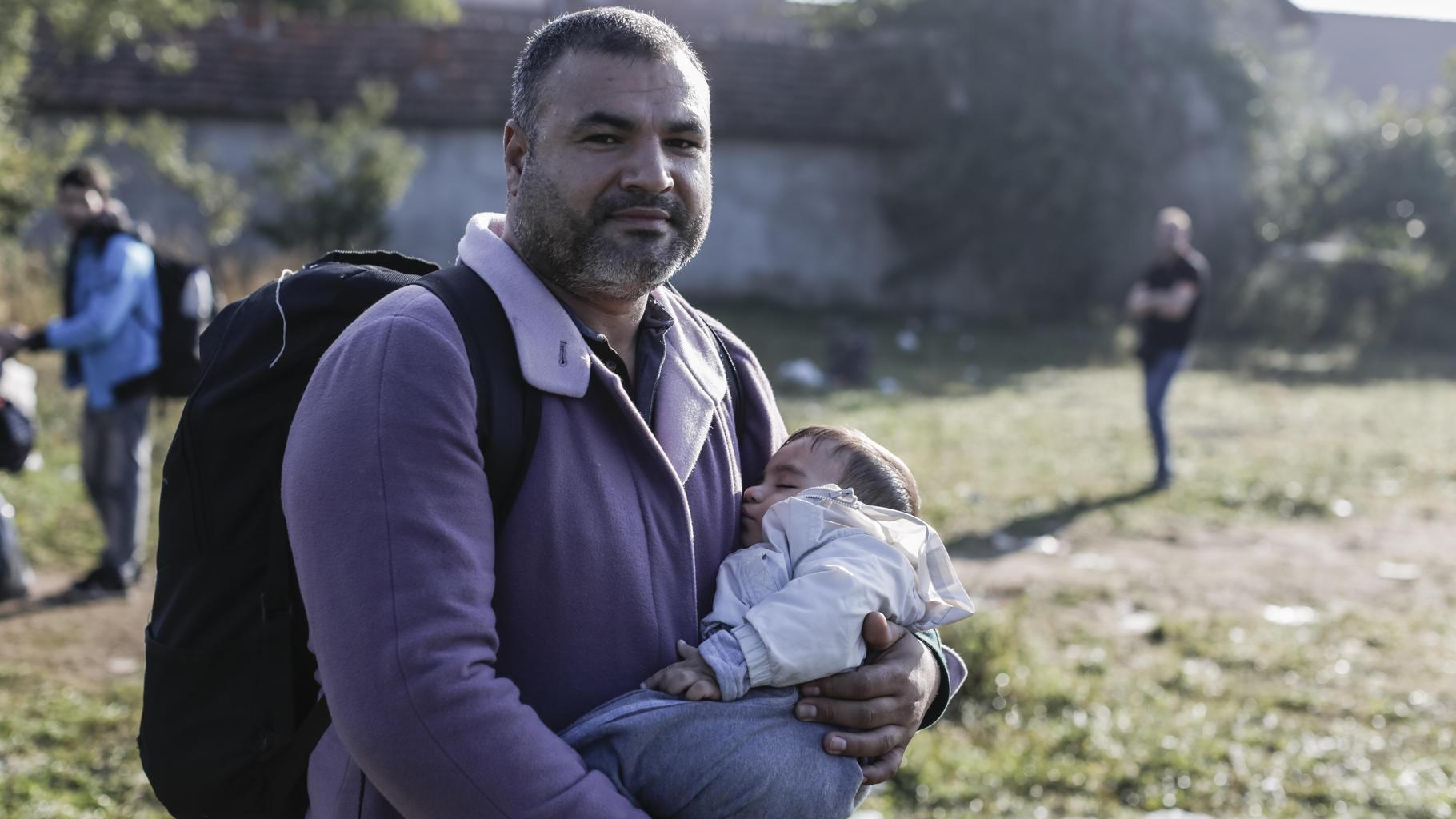 Yasser Hussein aus Homs, Syrien trägt seinen drei Monate alten Sohn.