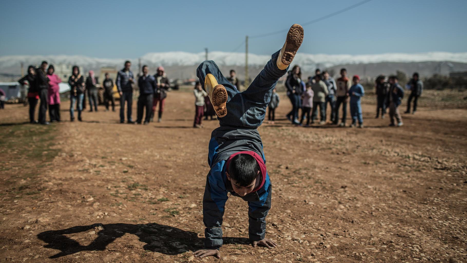 Ein Junge macht einen Handstand im Freien, während ca. 20 Menschen zuschauen.
