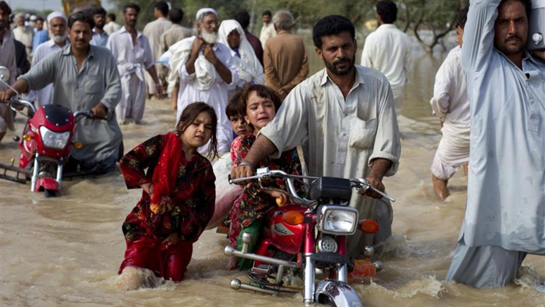 Foto: Ein Mann bringt seine Kinder in Sicherheit.