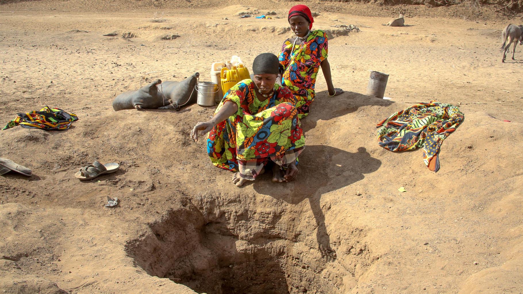 Zwei Frauen sitzen auf einem trockenem Boden vor einem gegrabenen Loch.