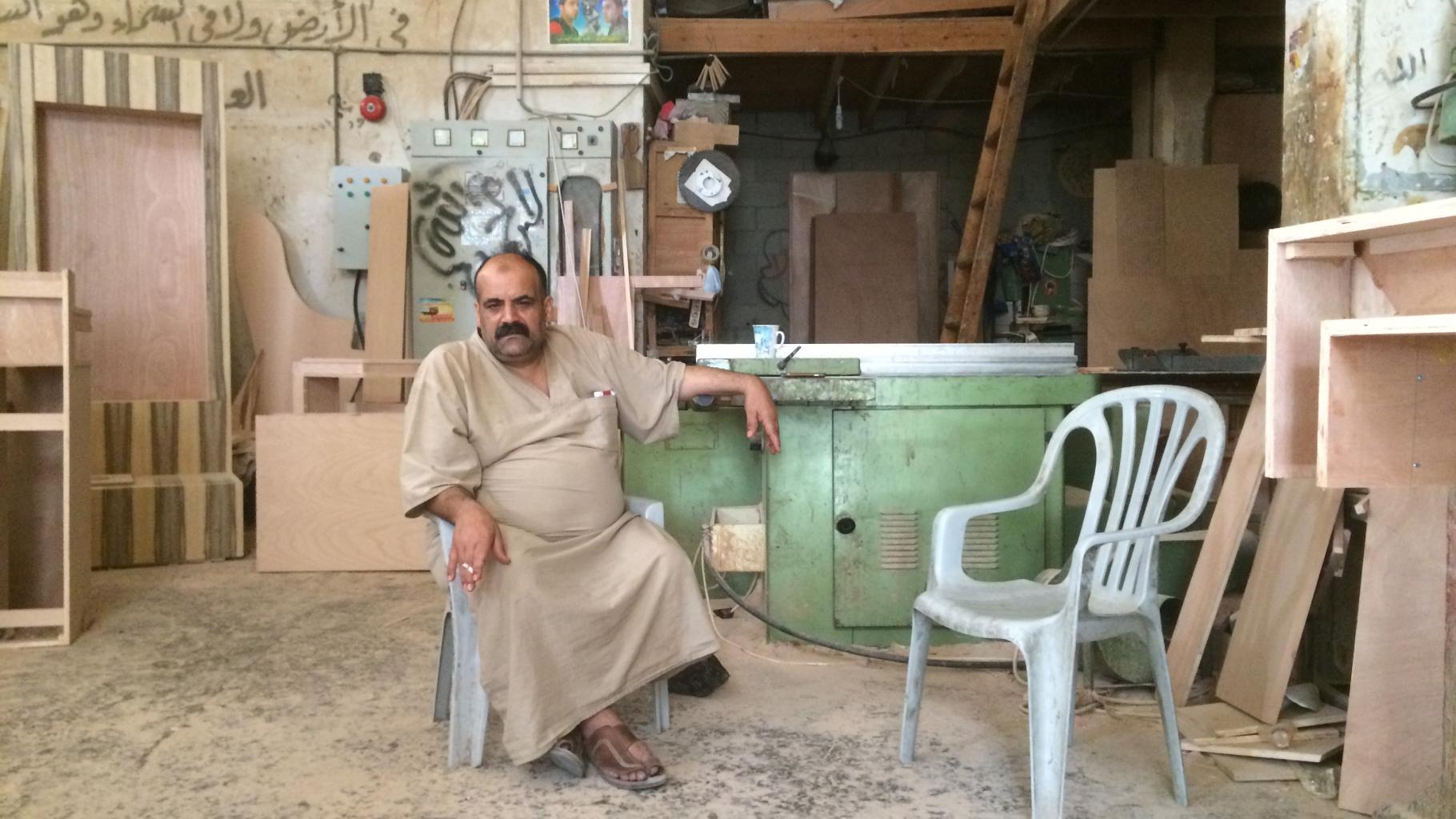 Ein Mann sitzt auf einem Plastikstuhl in einer Werkstatt mit Geräten, Brettern und Holzplatten.