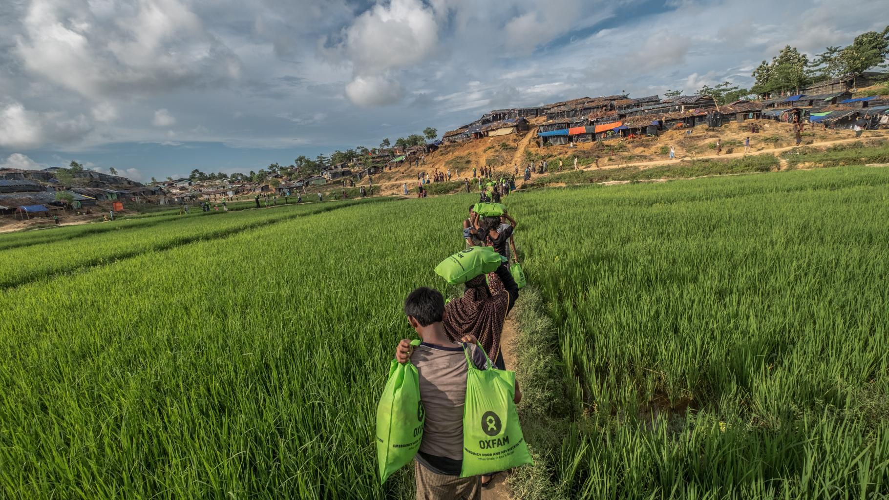 Menschen tragen Oxfam-Nahrungsmittelpakete durch ein Feld.