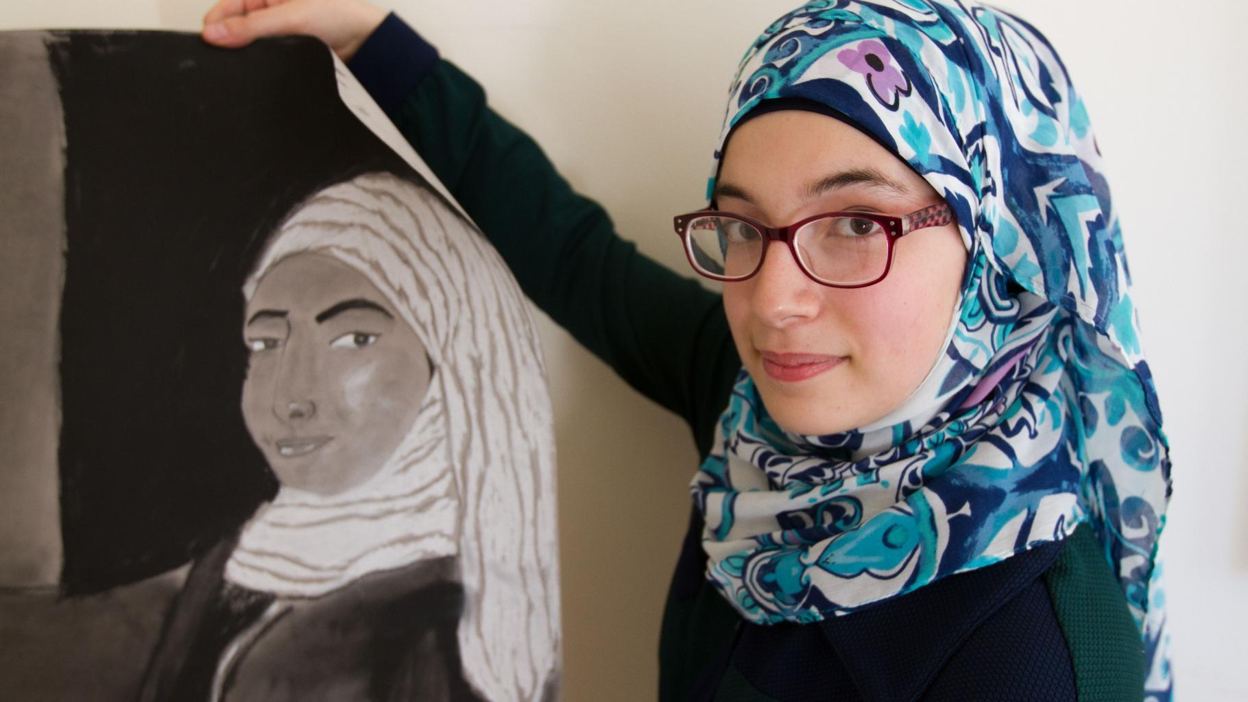 Eine junge Frau zeigt ein gezeichnetes Porträt einer Frau.