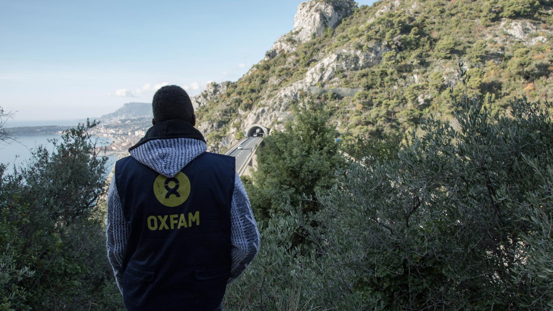 Oxfam-Mitarbeiter Adoum Ismail steht an der Grenze zu Frankreich und Italien und betrachtet eine Autobahnbrücke..