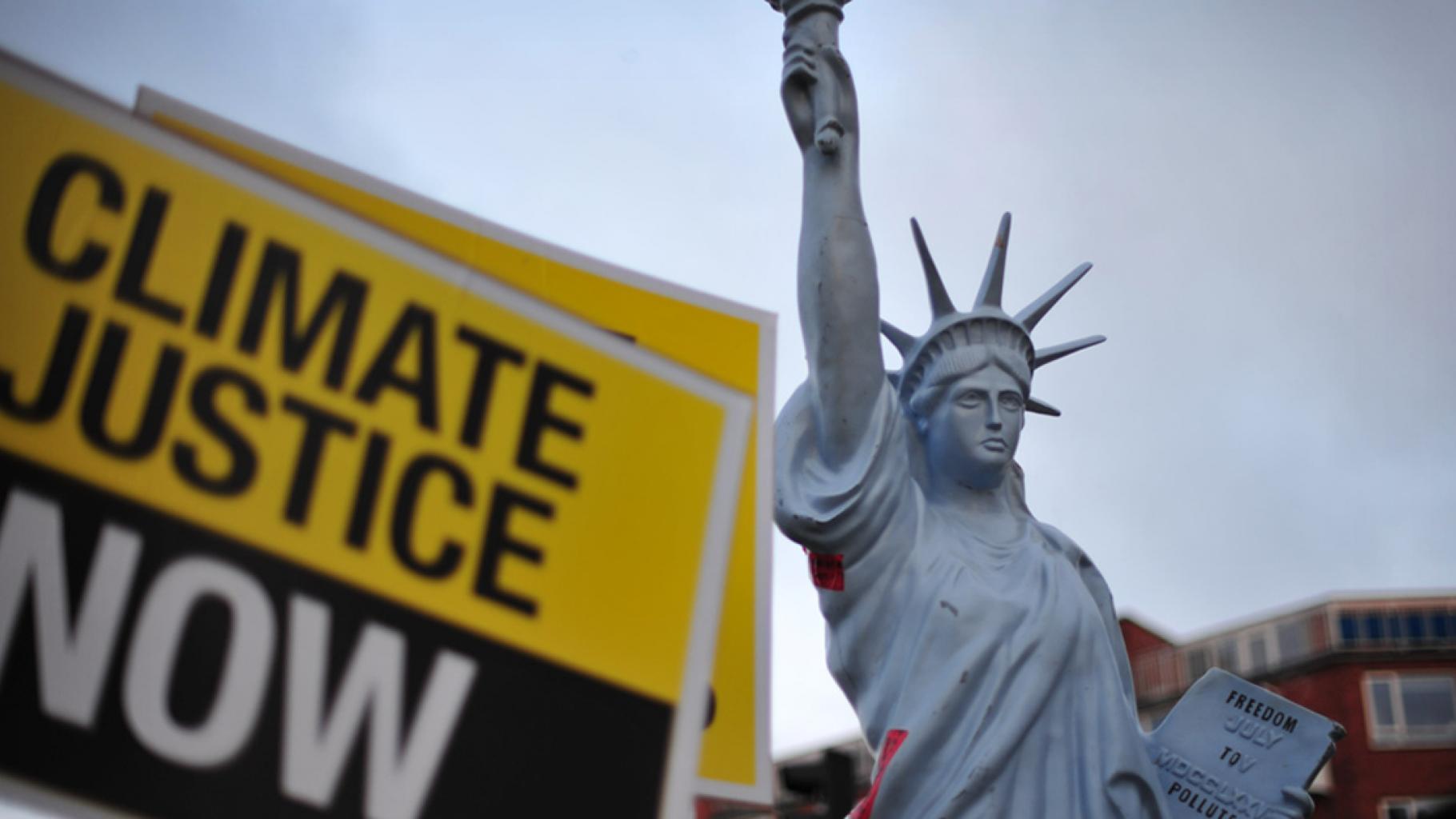 """Ein Schild mit der Aufschrift """"Climate Justice Now"""" hinter einem Modell der Freiheitsstatue"""