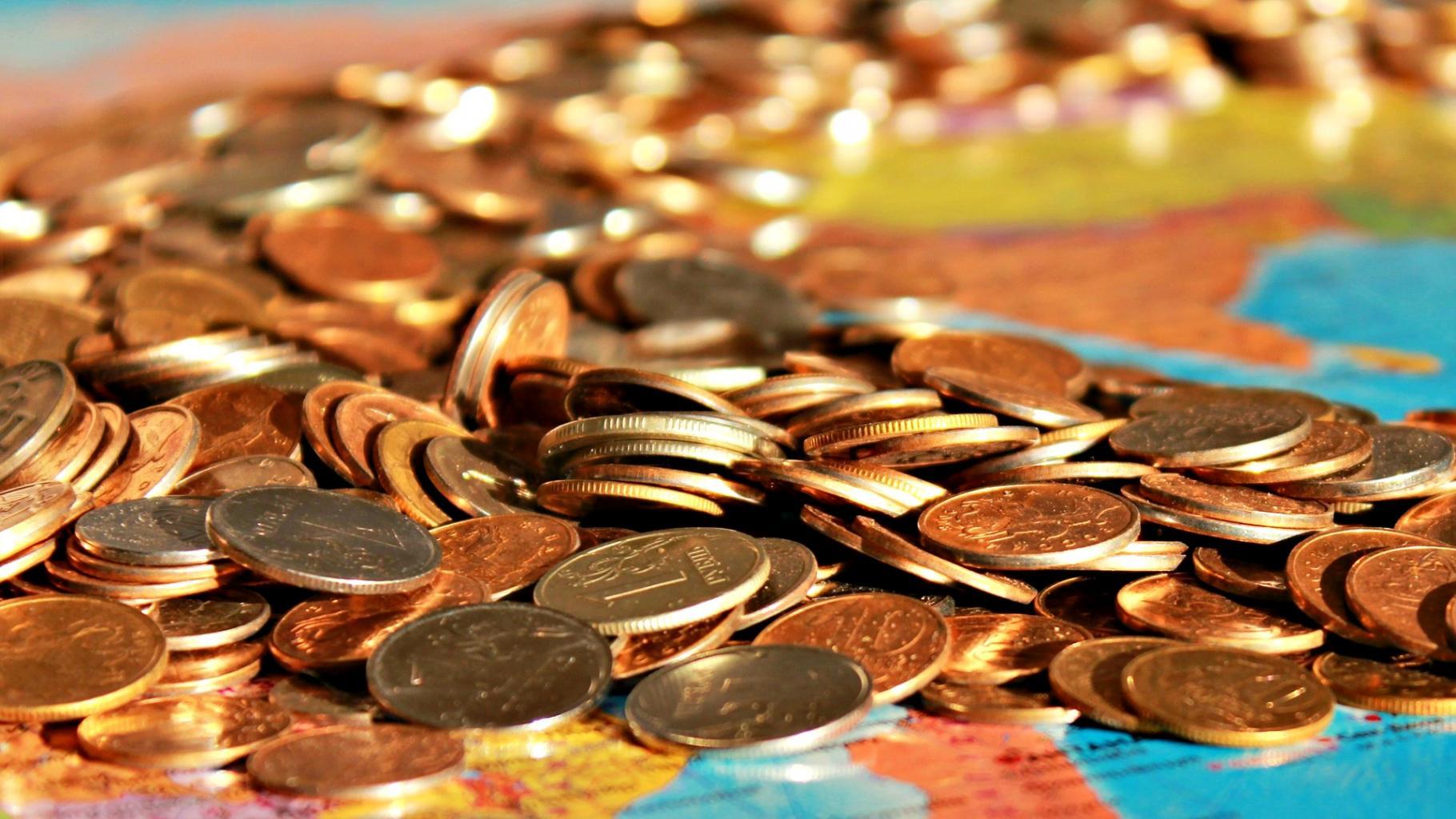 Münzen auf einer Weltkarte.