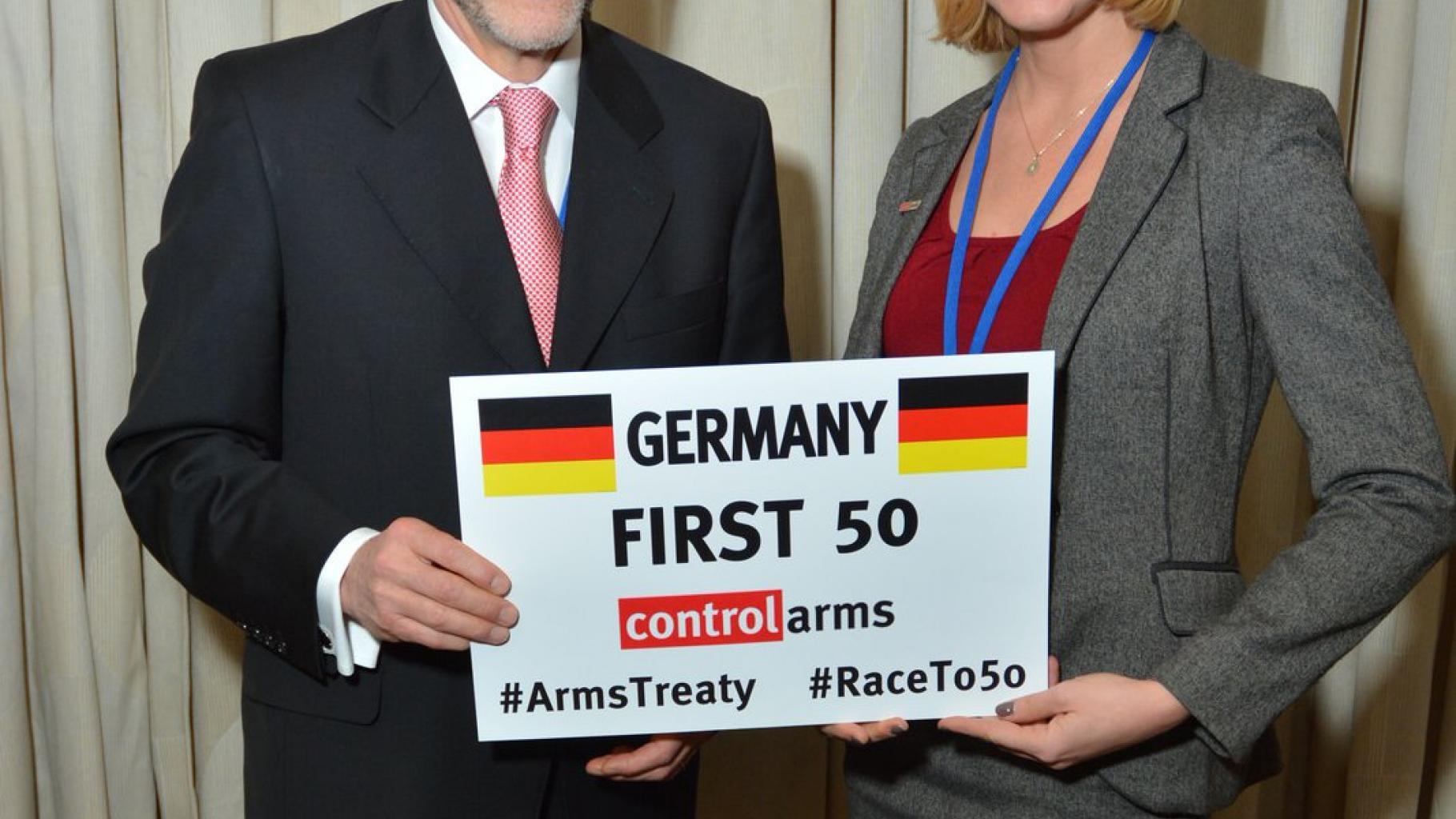 Harald Braun und Allison Pytlak halten Schild mit Aufschrift: Germany – first 50