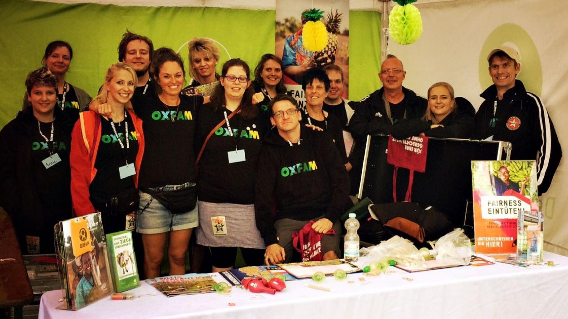 Ein Team von Konzertaktivist/innen an einem Oxfam-Stand